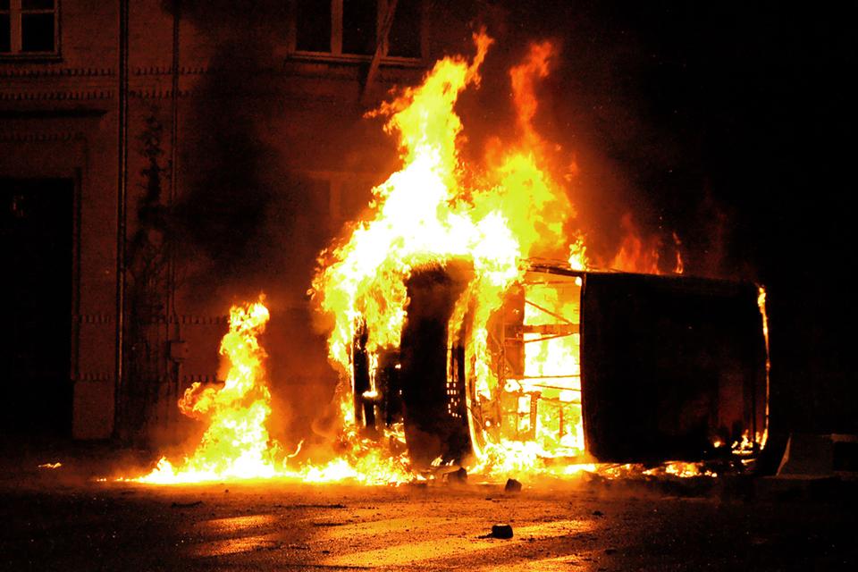 Zdjęcie przedstawia płonący samochód wcentrum miasta. Noc. Samochód leży na prawym boku. Wrak samochodu bez szyb. Samochód cały wpłomieniach. Rozlana benzyna wokół samochodu. Płomienie na powierzchni rozlanej benzyny. Wtle kamienica.