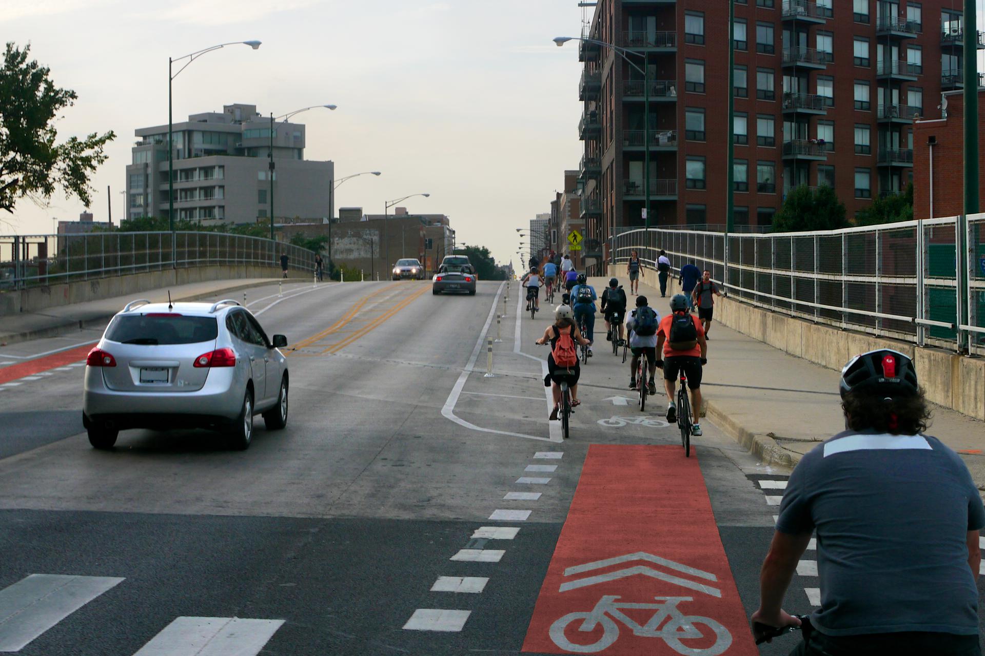 Zdjęcie pasa rowerowego rowerowej zwidocznym znakiem ijadącym rowerzystą, obok jadący samochód
