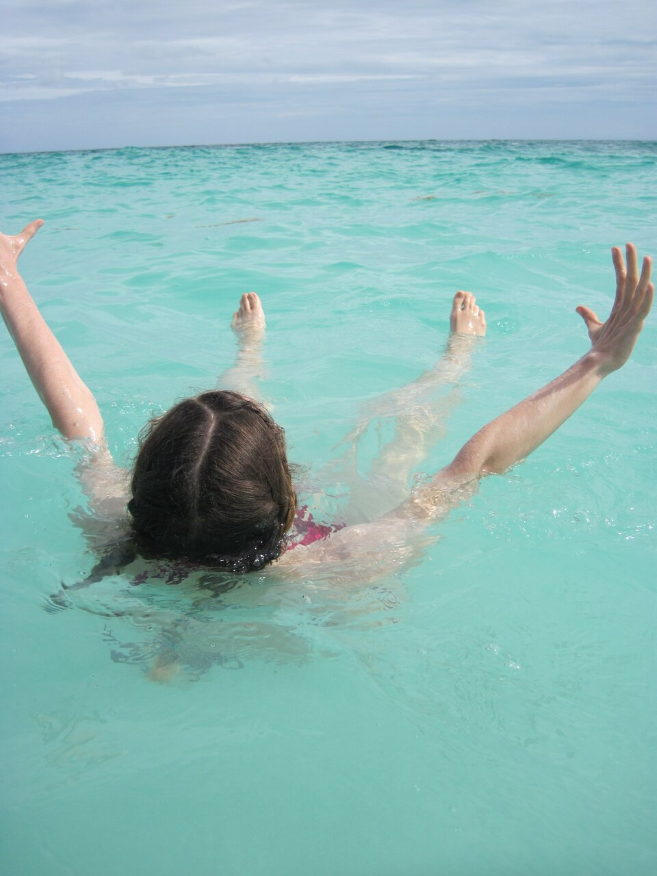 Na zdjęciu osoba unosząca się na powierzchni słonej wody wmorzu. Woda wmorzu jasnoniebieska.