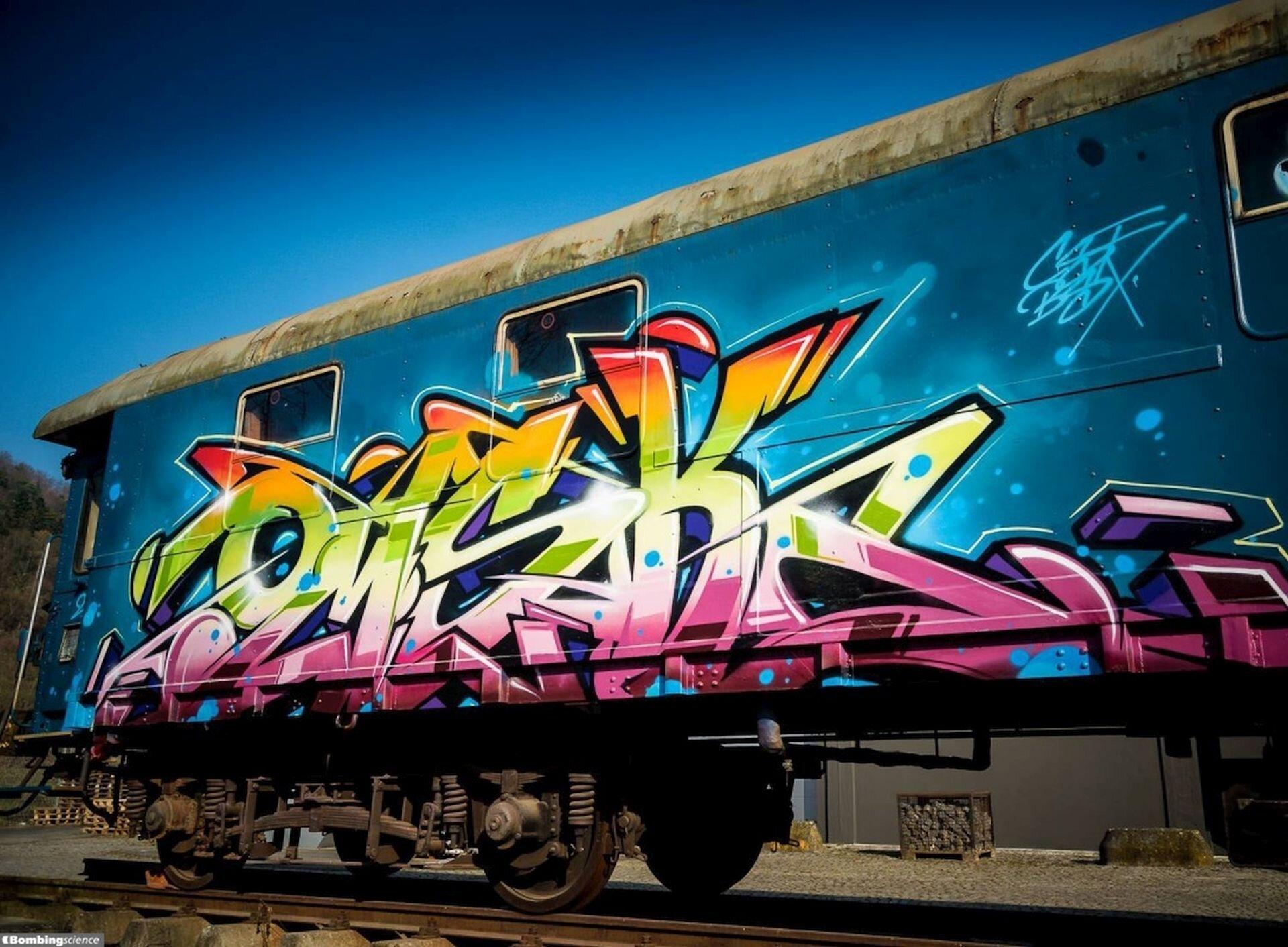 Ilustracja przedstawia graffiti namalowane na niebieskim wagonie. Jest to wielobarwny napis wkolorach: czerwonym, pomarańczowym, żółtym, zielonym, białym iróżowym otoczony czarnym konturem. Wtle rozciąga się niebieskie, bezchmurne niebo.