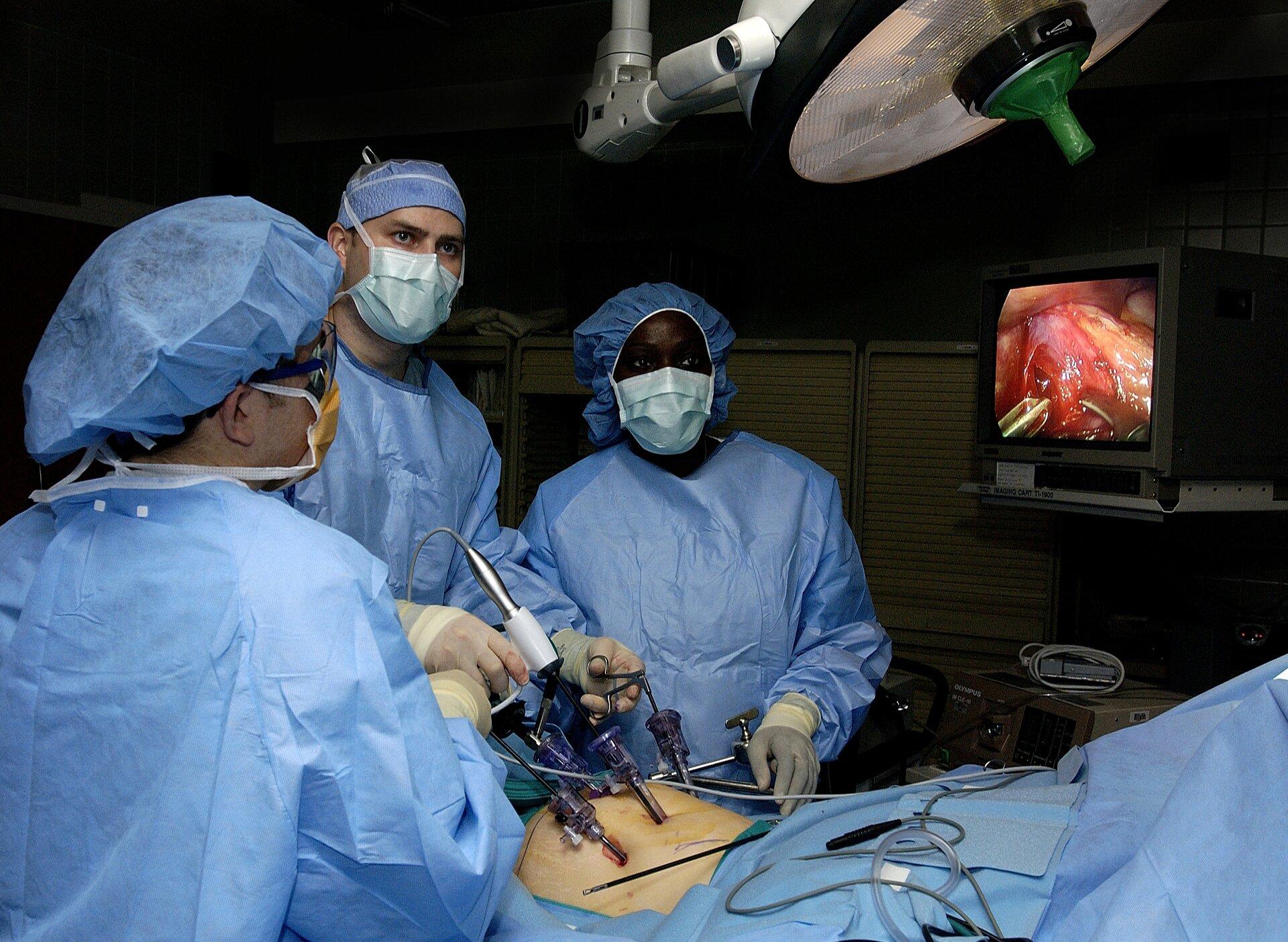 Fotografia przedstawia lekarzy wtrakcie operacji laparoskopowej jamy brzusznej pacjenta, okrytego niebieskimi chustami. Troje lekarzy ubranych jest wniebieskie kitle. Nad nimi lampa operacyjna. Zprawej monitor, na którym wdużym powiększeniu można obserwować postęp operacji.