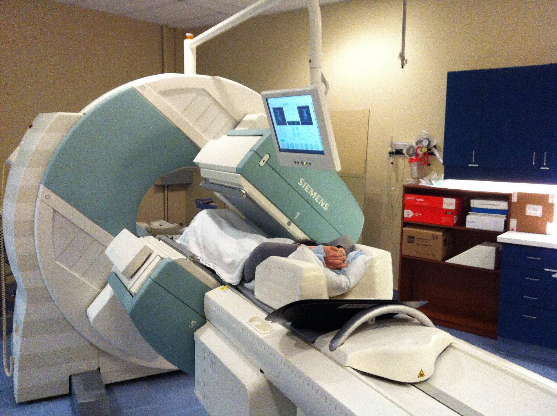 Na zdjęciu wnętrze gabinetu diagnostycznego. Na środku tomograf. Duże koło zotworem pośrodku. Na ruchomej części tomografu leży pacjent. Na monitorze obraz diagnozowanego narządu pacjenta. Zprawej strony inne wyposażenie gabinetu, regały zsegregatorami.
