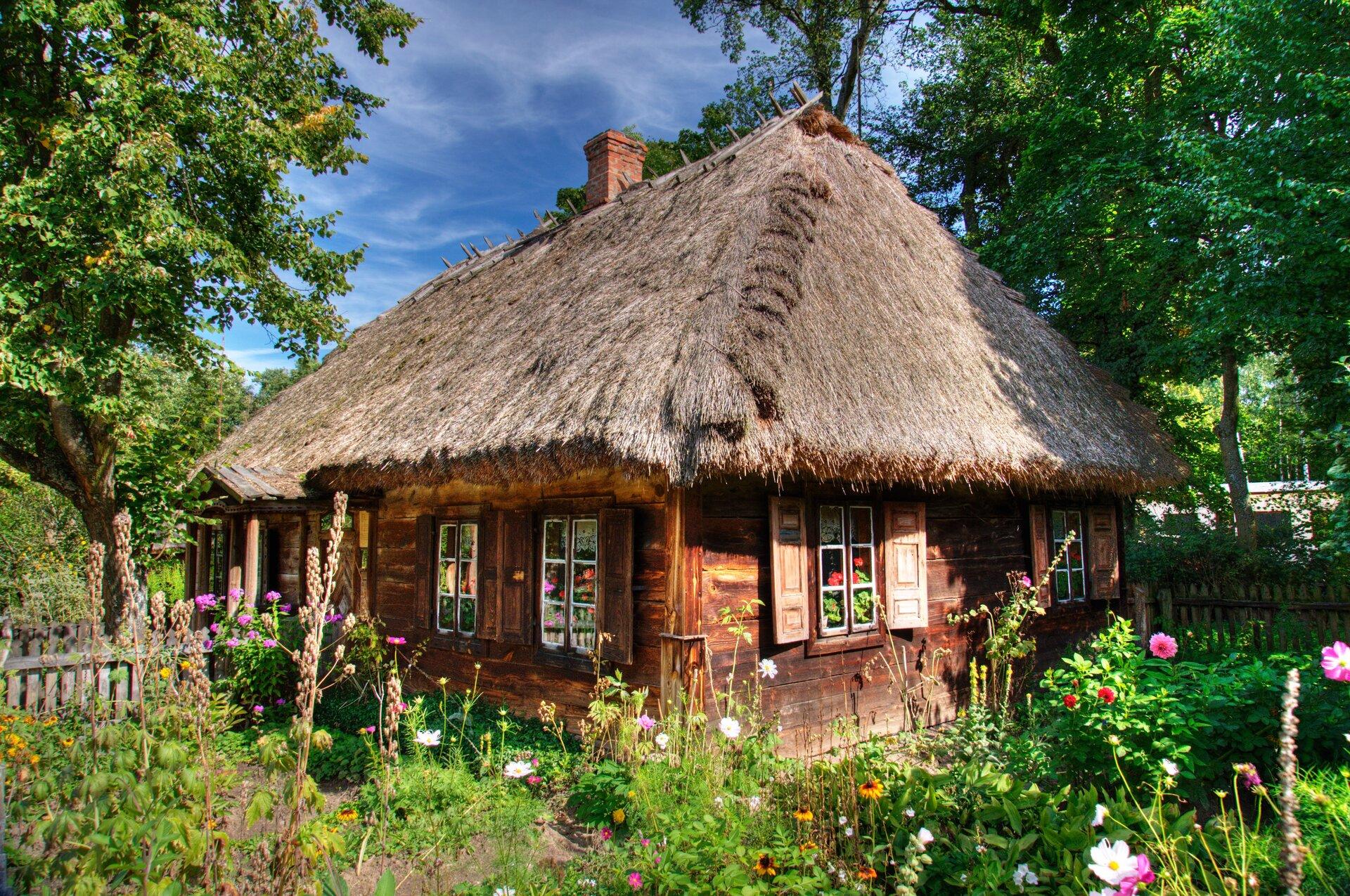 Stojąca wogrodzie zarośniętym kolorowymi kwiatami drewniana chata pokryta słomianą strzechą. Wchacie, woknach też są kwiaty.