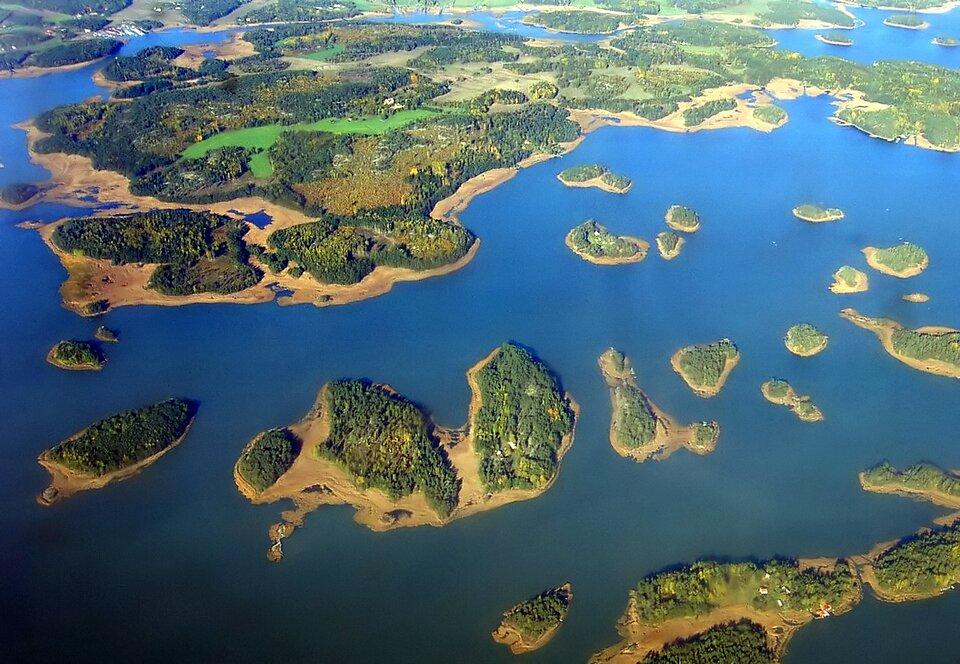 Na zdjęciu wiele małych wysepek porośniętych lasem, brzegi piaszczyste. Widok zgóry.
