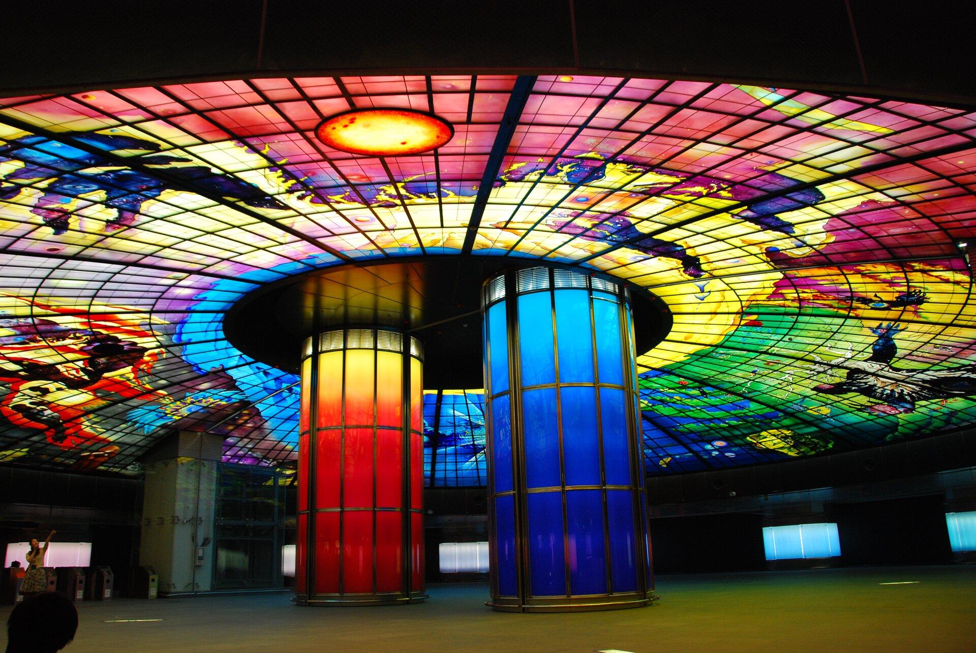 Zdjęcie przedstawia Kopułę Światła na stacji metra Bulwaru Formosa. Jest to największa szklana konstrukcja na świecie zajmująca obszar 2180 metrów kwadratowych izbudowana z4,5 tysiąca szklanych płyt. Na zdjęciu pokazana jest część centralna wpostaci dwóch kolumn, czerwonej iniebieskiej, podtrzymujących sklepienie, na którym wszkle zaprezentowano różnobarwne obrazy.