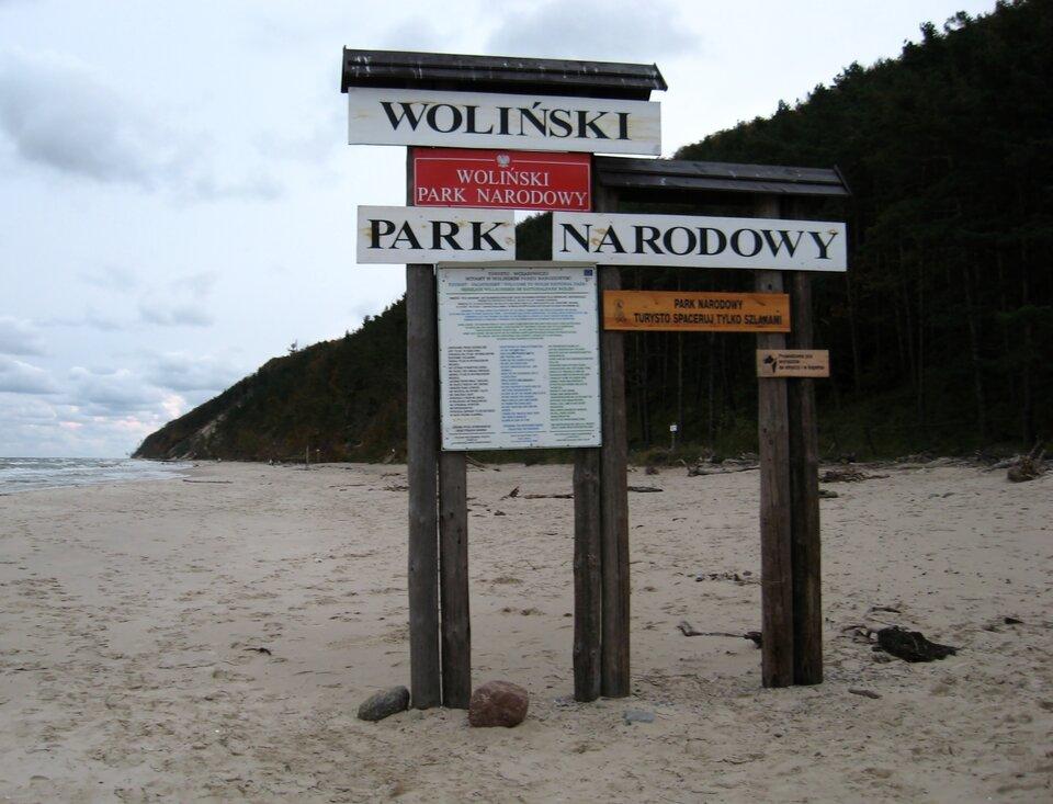 Na zdjęciu tablica informacyjna na plaży. Drewniane słupki, daszek. Napisy iinformacje.
