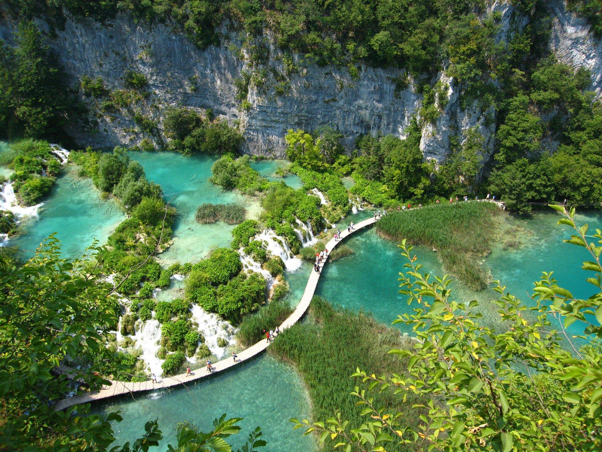 Fotografia druga wykonana zwysokości prezentuje jeziora zturkusowymi wodami umiejscowione pomiędzy skałami.