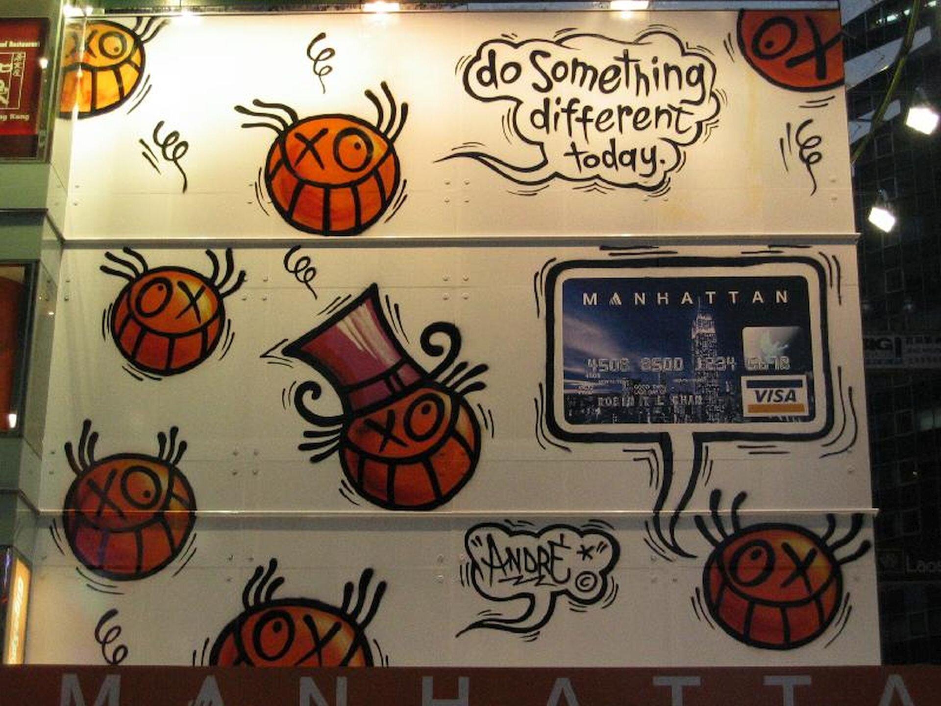 """Ilustracja przedstawia reklamę karty płatniczej wykonaną techniką graffiti. Ukazuje animowane twarze oraz kartę płatniczą, umieszczoną wdymku na białym tle. Symboliczne twarze są pomarańczowe, wszystkie mają znakiem xoznaczone przymknięte oko iszeroki uśmiech zzębami. Jedna znich ma na głowie cylinder. Na karcie bankomatowej widnieje napis """"Manhattan"""", powyżej namalowana jest chmurka wktórej zamieszczony jest napis """"Do something different today""""."""