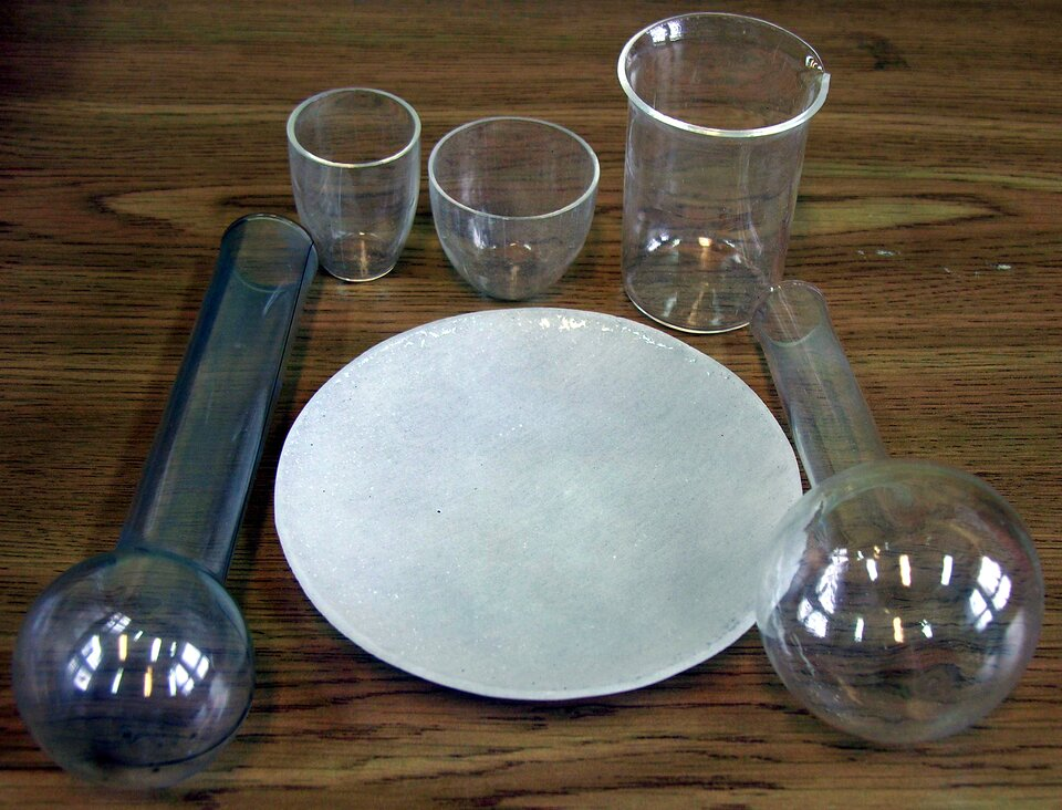 Zdjęcie przedstawia szklane naczynia laboratoryjne. Dwie leżące płasko kolbki kuliste zokrągłymi szyjkami, pomiędzy nimi talerzyk zbłyszczącym szkliwem, powyżej trzy naczynia stojące, wtym dwa tygielki ijedna zlewka.