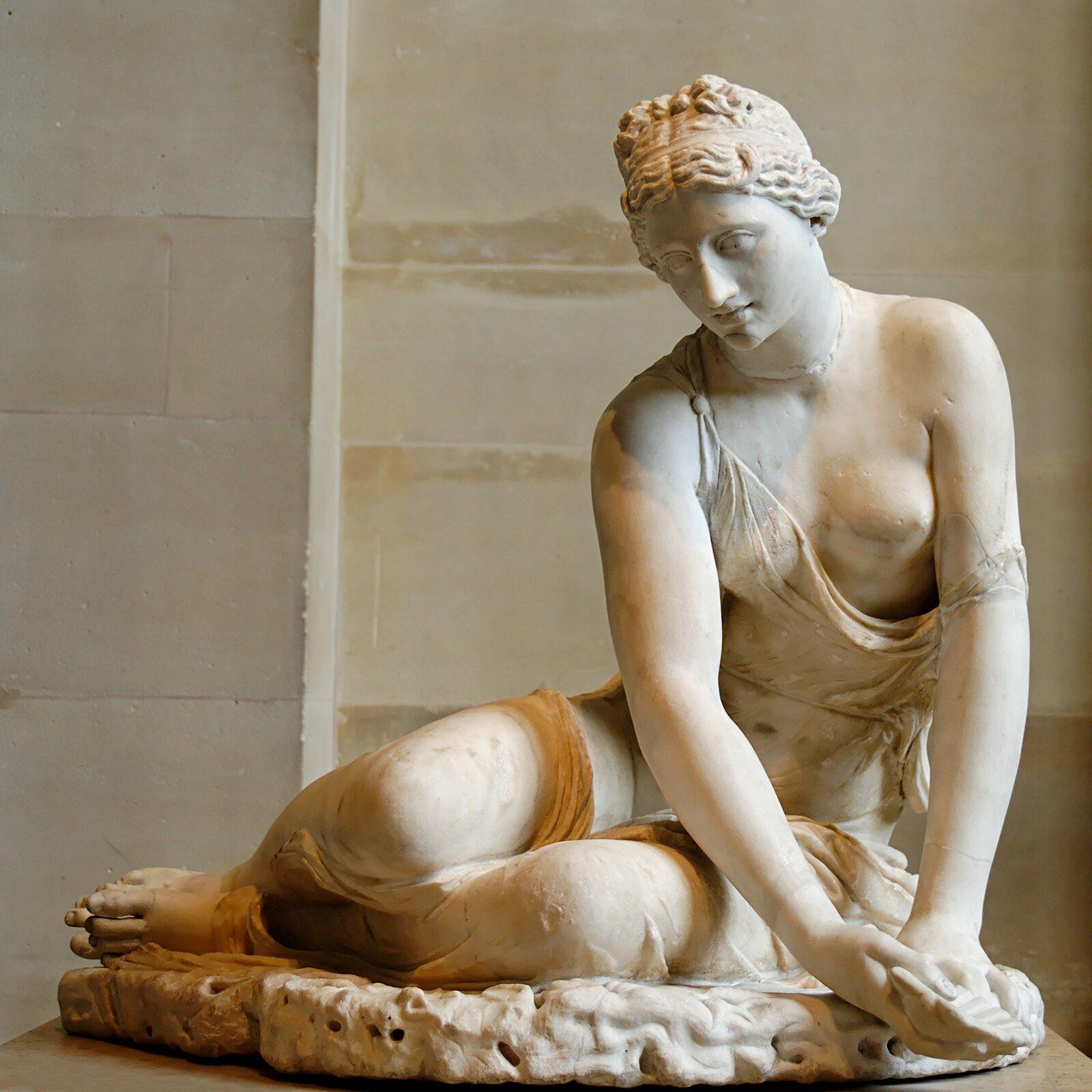 Ilustracja przedstawia rzeźbę kobiety-nimfy siedzącej na ziemi. Kobieta ma spięte włosy iubrana jest wlekką szatę, która zsunęła się zjej lewego ramienia, odsłaniając pierś. Wdłoniach nimfa trzyma muszlę. Rzeźba została wykonana zbiałego marmuru.