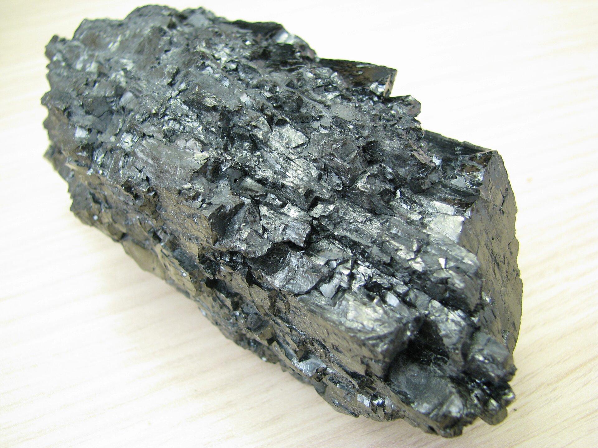 Na zdjęciu przedstawiona jest bryła węgla kamiennego – ma czarną barwę, matowy połysk.