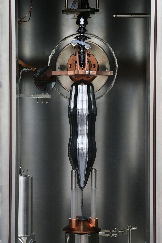 Zdjęcie przedstawia proces tworzenia podłużnego, cylindrycznego monokryształu krzemu metodą Czochralskiego. Znajduje się na nim cylindryczne wnętrze pieca indukcyjnego ztyglem wdolnej części, zktórego po podgrzaniu wyciągana jest nić kryształu, która nieco wyżej zwijana jest wcoraz szerszy monokryształ. Kryształ na zdjęciu jest czarny ibłyszczący, ajego kształt przypomina odwróconą do góry nogami, zwężoną wsamym środku butelkę coca coli, lecz obardzo krótkiej, szpiczastej szyjce. Od góry wisi on również na nitce krystalicznej rozszerzającej się wformę onieregularnym kształcie iprzymocowaną do elementu rozciągającego.