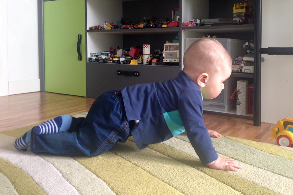 Fotografia przedstawia dziecko raczkujące po dywanie wprawo wstronę zabawki. Rozwija zdolności motoryczne. Wtle ciemny regal zzabawkami.