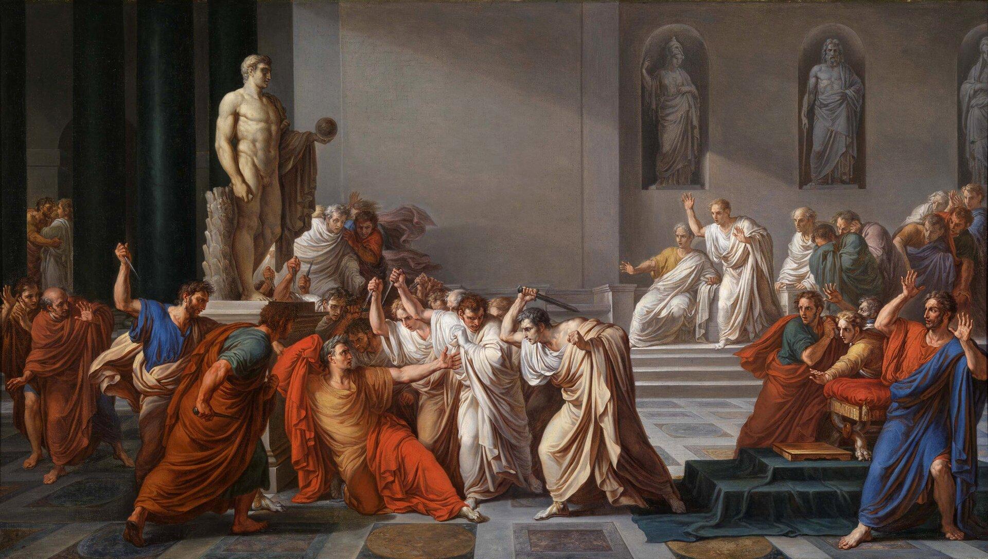 """Na ilustracji przedstawione jest dzieło Vincenzo Camuccini' ego pt. """"Zabójstwo Juliusza Cezara"""". Na pierwszym planie ukazana jest postać Cezara wotoczeniu spiskowców. Cesarz ubrany jest wbrązowe szaty. Upada pod ciosami zabójców, którzy otaczają go ze wszystkich stron. Tło obrazu stanowi wnętrze senatu: marmurowe schody iposągi."""