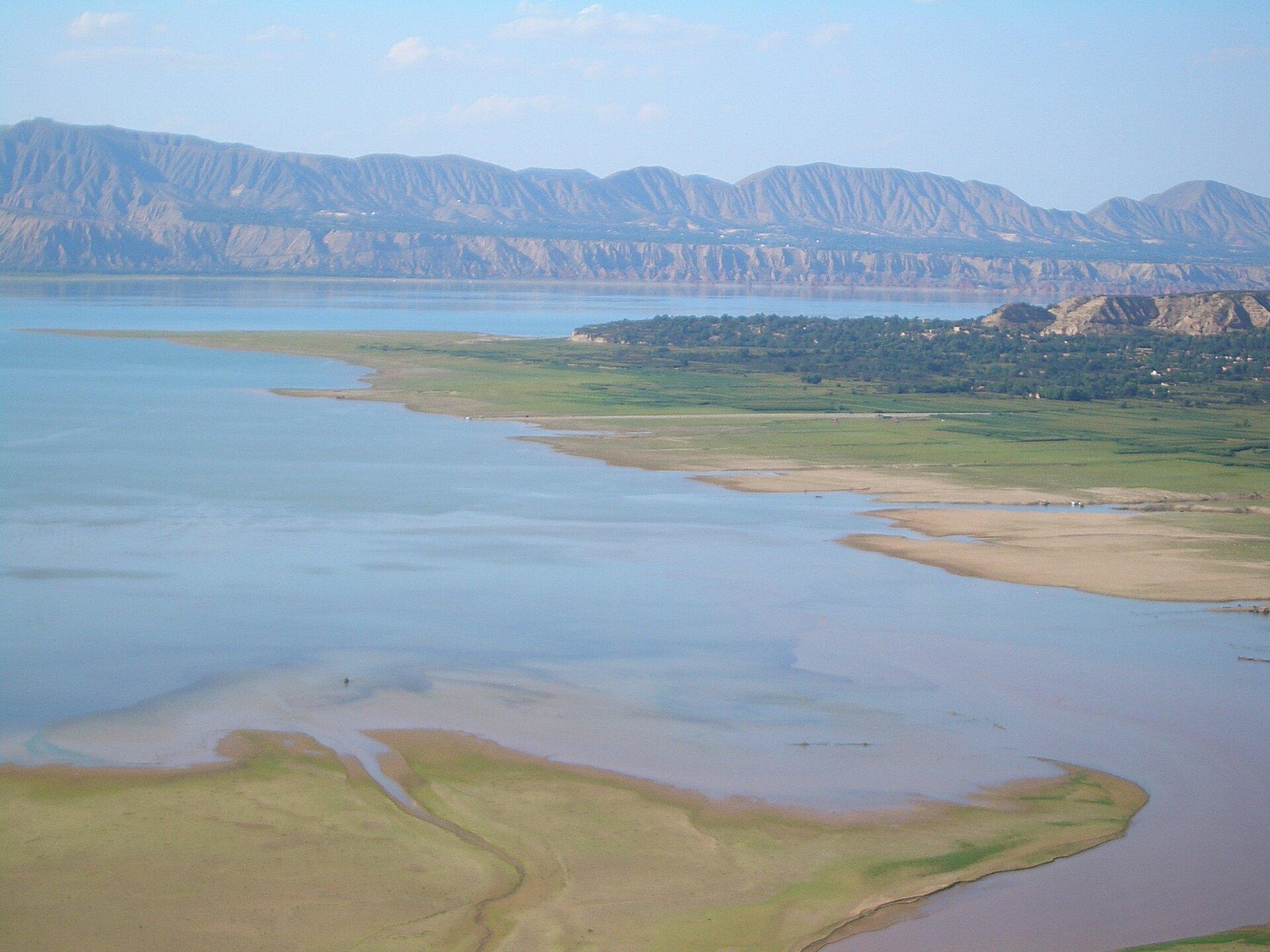 Na zdjęciu rozległa rzeka wszerokiej dolinie, przy brzegu osady. Wtle pasmo górskie pozbawione roślinności.