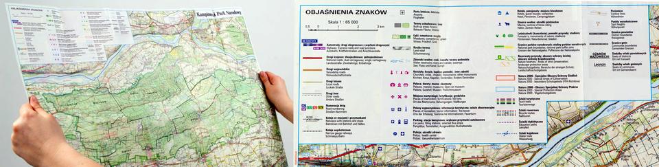 Zdjęcie przedstawia mapę turystyczną. Mapa ma kształt prostokąta. Mapa trzymana jest za boki, widać dwie dłonie po lewej iprawej stronie mapy. Dłuższe boki ułożone są poziomo. Wlewym górnym rogu znajduje się legenda. Obok legenda przedstawiona jest wpowiększeniu. Jest to biały prostokąt zwyciętym rogiem, na którym znajduje się skala jeden do sześćdziesięciu pięciu tysięcy, podziałka liniowa iobjaśnienia znaków użytych na mapie. Na mapie kolorowe przerywane linie oznaczają szlaki turystyczne. Miejsca zakreślone owalnymi liniami izacieniowane na niebiesko to jeziora, stawy, niebieskie linie to rzeki. Białe miejsca na mapie to pola uprawne. Zielone plamy oznaczają tereny leśne. Szczyty są nazwane oraz podana jest liczba metrów opisanego wzniesienia. Cała mapa pokryta jest jasno brązowymi liniami, które ułożone wformie pętli. Linie mają kształt falisty. Są to poziomice. Im mniejsza odległość między liniami tym powierzchnia terenu jest bardziej stroma.