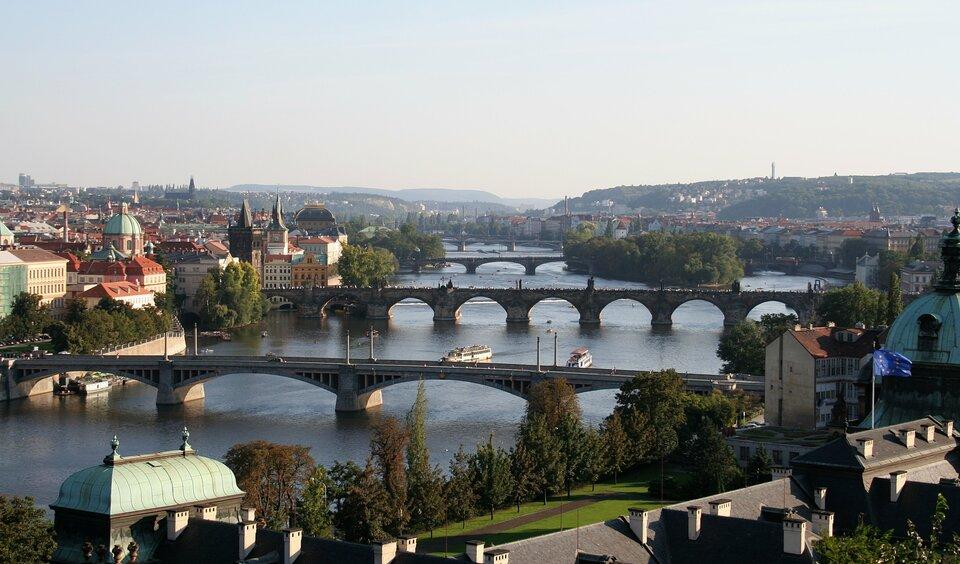 Widok zlotu ptaka na szeroką rzekę. Na rzece kilka mostów. Po obydwu stronach rzeki staromiejska zabudowa.