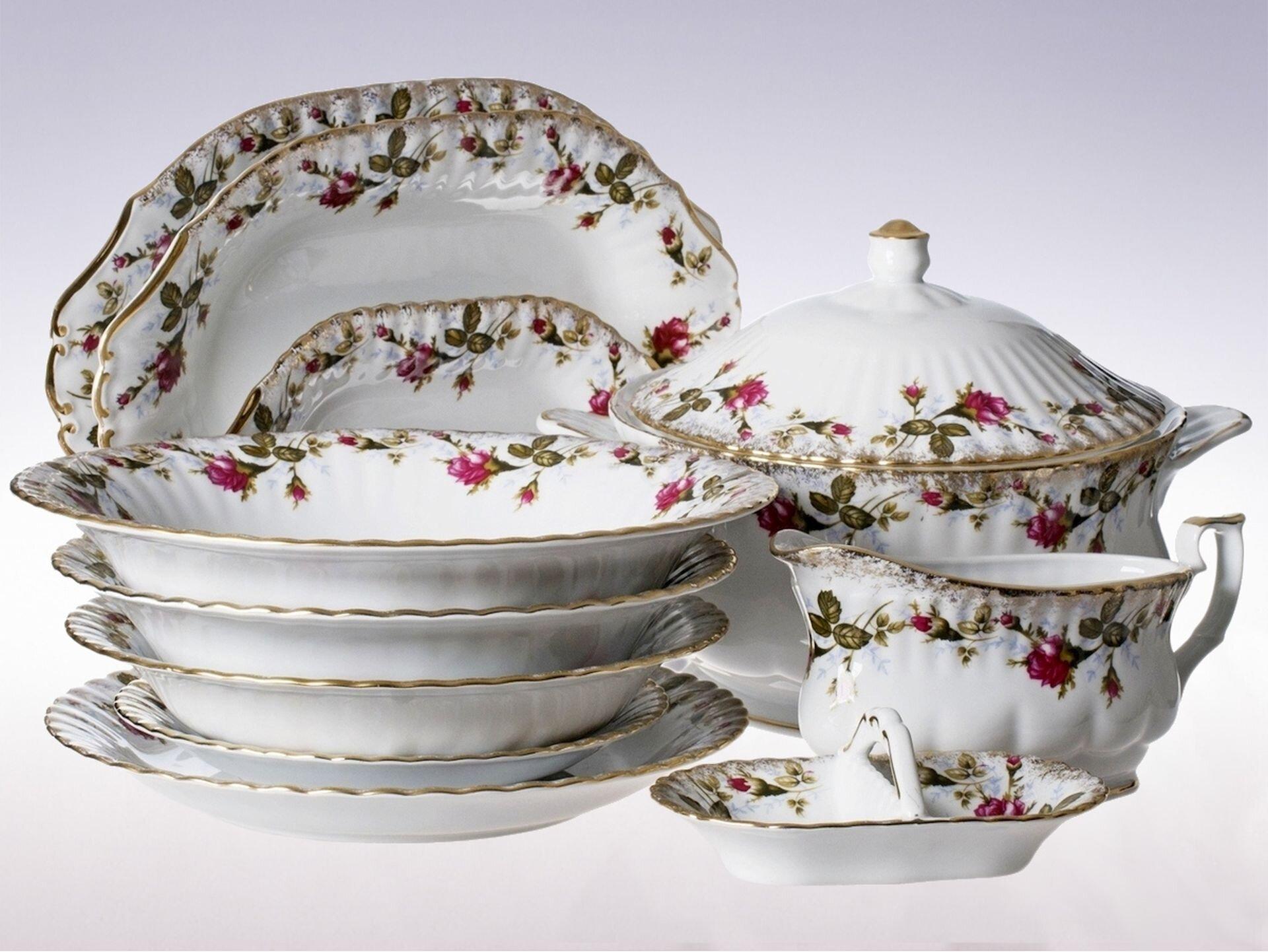 Ilustracja przedstawia porcelanę zĆmielowa. Jest to zestaw talerzy, waza, sosjerka. Porcelana jest biała zdobiona bordowymi kwiatami na bokach, abrzegi są pomalowane złotym kolorem.