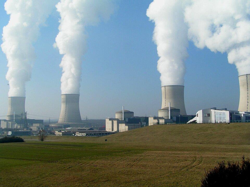 Kolorowe zdjęcie przedstawia budynki ichłodnie elektrowni atomowej wCattenom. Słoneczny dzień. Na pierwszym planie szeroki płaski teren pokryty zielono-żółtą krótką trawą. Chłodnie elektorowi mieszczą się wgłębie. Ich kształt można określić jako cylindryczny. Biała gęsta para wydobywa się zchłodni ipionowo wzbija się wgórę. Pomiędzy chłodniami niskie zabudowania elektrowni.