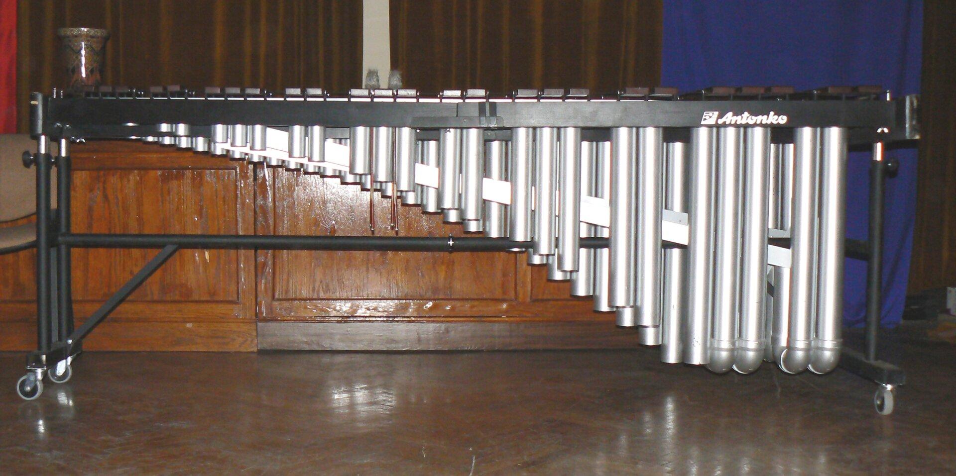 Na zdjęciu marimba. Instrument składa się zwielu drewnianych sztabek zamontowanych na metalowym statywie. Pod sztabkami znajdują się metalowe rury.