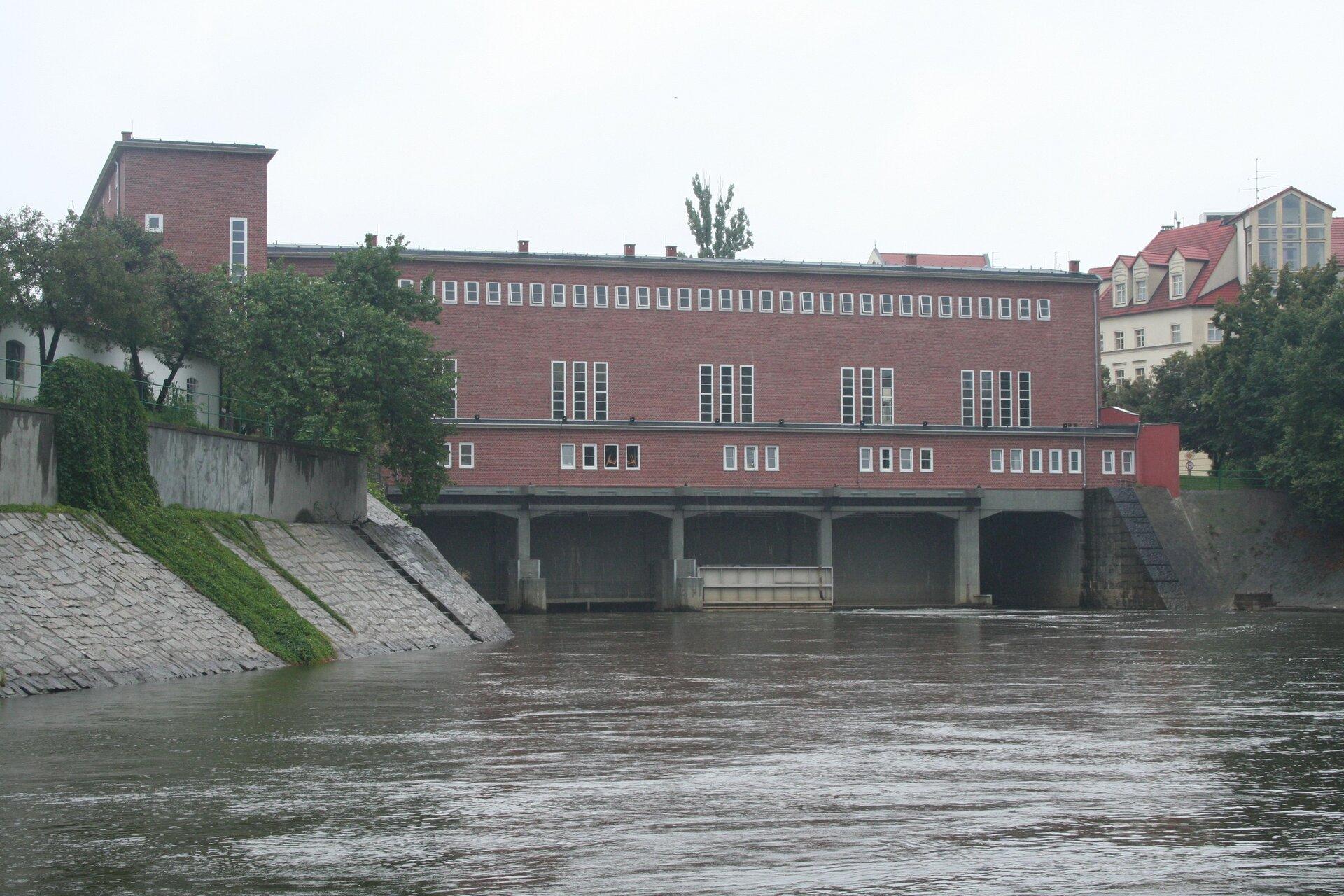 Na zdjęciu rzeka we wzmocnionym murowanym korycie. Nad nią przepływowa elektrownia wodna, ceglany budynek.