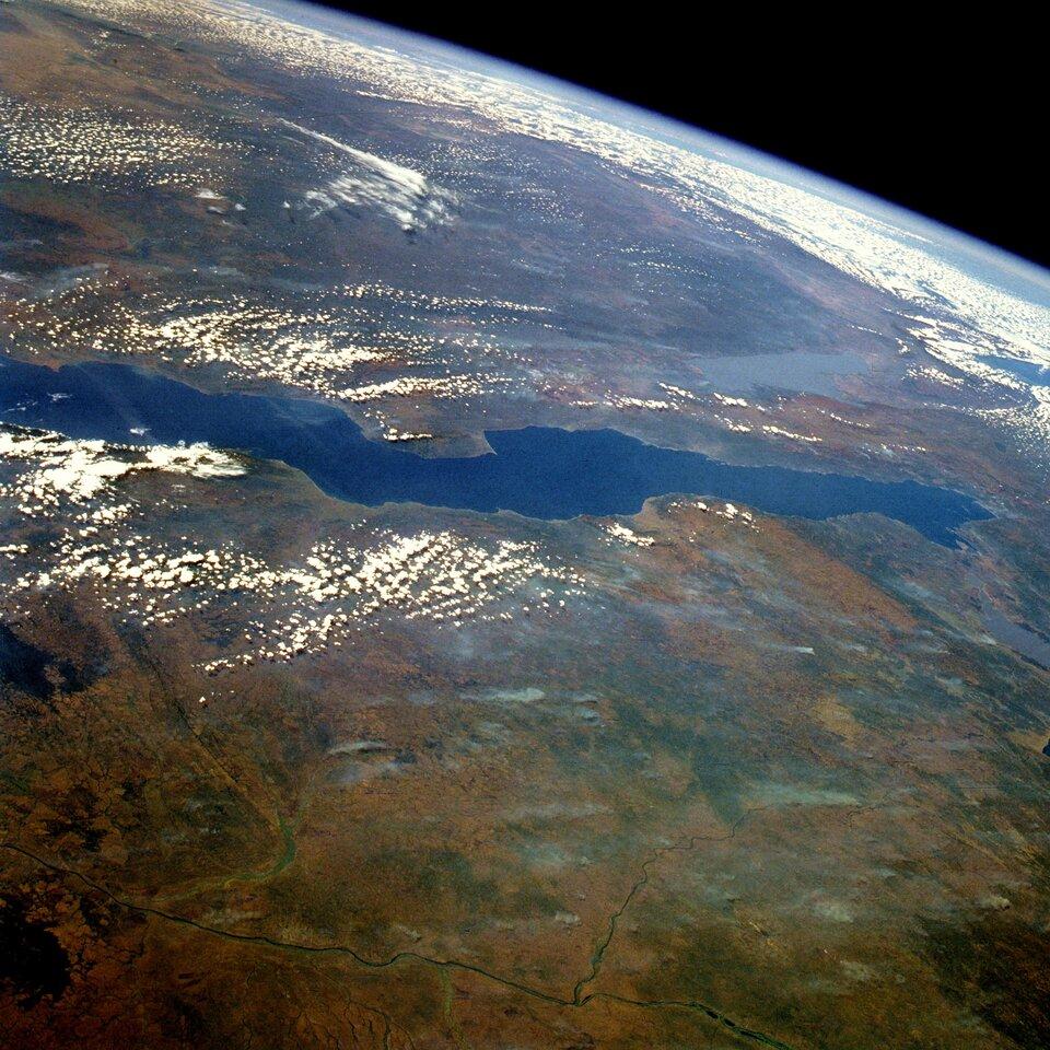 Na zdjęciu satelitarnym bardzo długie jezioro onieregularnej linii brzegowej.