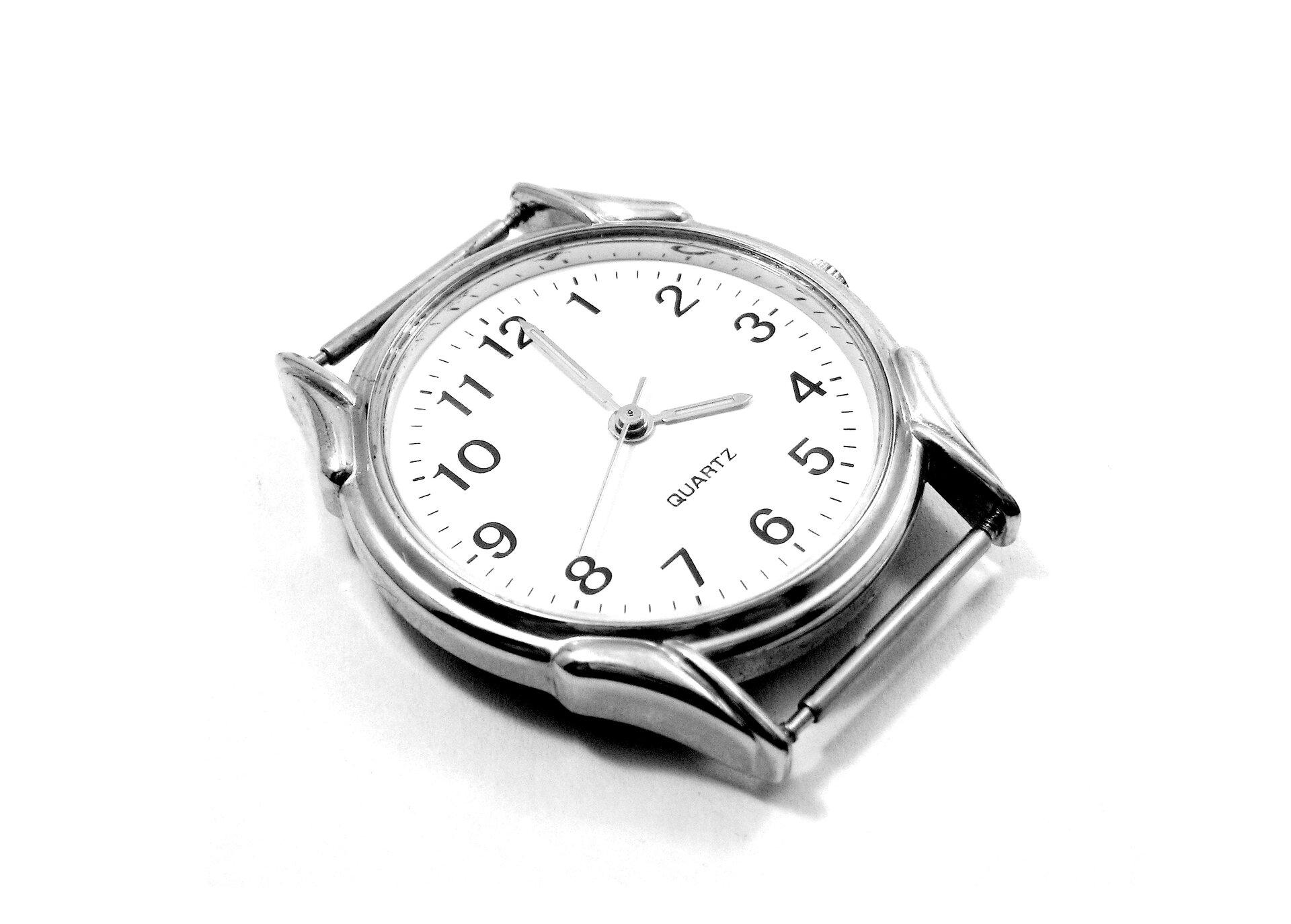 Zdjęcie przedstawia zegarek ręczny bez paska. Koperta metalowa, srebrna, podobnie wskazówki. Cyferblat biały zczarnymi cyframi arabskimi. Pomiędzy cyframi 8 i4 widoczny napis QUARTZ.