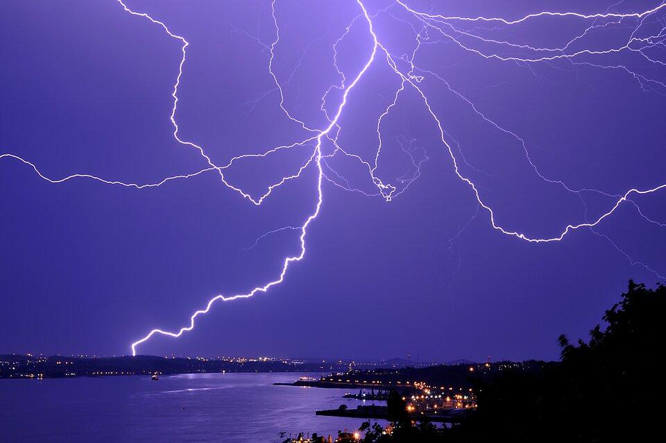 Na fotografii widoczne nocne bezchmurne niebo zrozbiegającymi się wróżnych kierunkach białymi błyskawicami