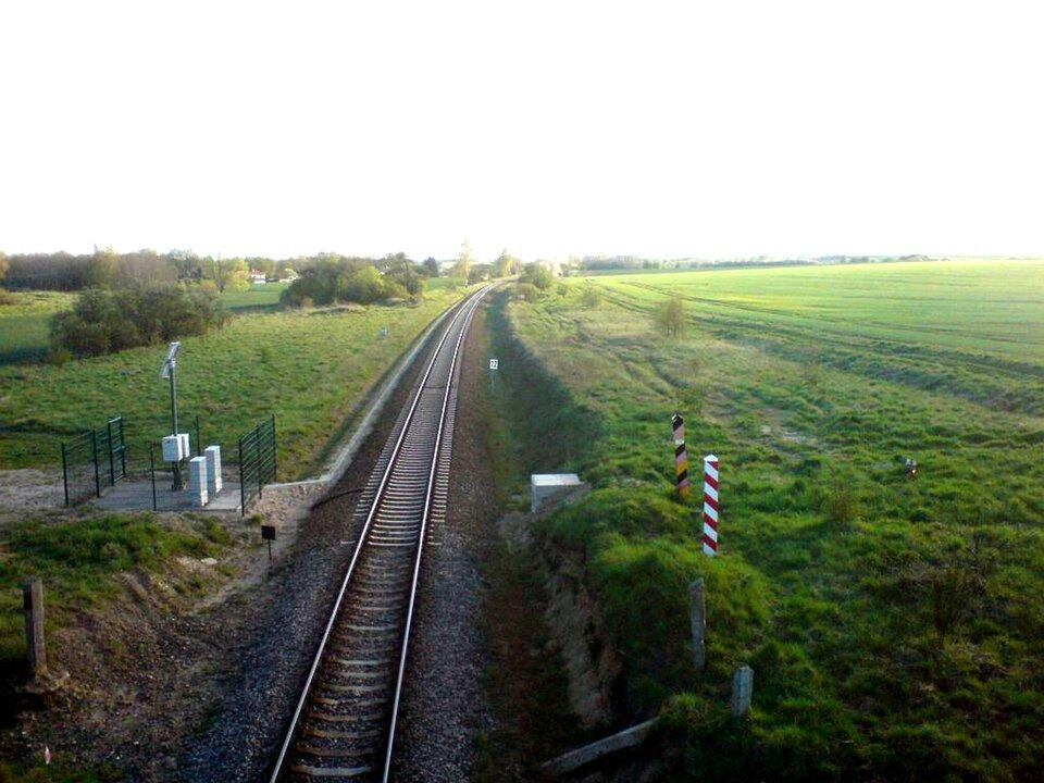 Na zdjęciu tory kolejowe wpłaskim trawiastym terenie. Po prawej stronie dwa słupki, jeden wbiało-czerwone pasy, drugi – wczarno-czerwono-żółte.