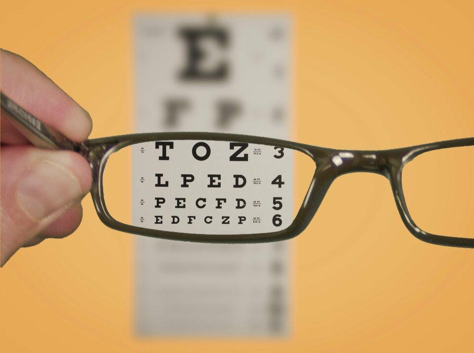 Zdjęcie przedstawia rozmytą tablicę optyczną do badań wzroku wiszącą na żółtej ścianie. Na pierwszym planie palce lewej dłoni trzymają wyciągnięte okulary. Fragment tablicy oglądany przez szkła jest ostry. Można odczytać litery na liniach testowych 3, 4, 5 i6.