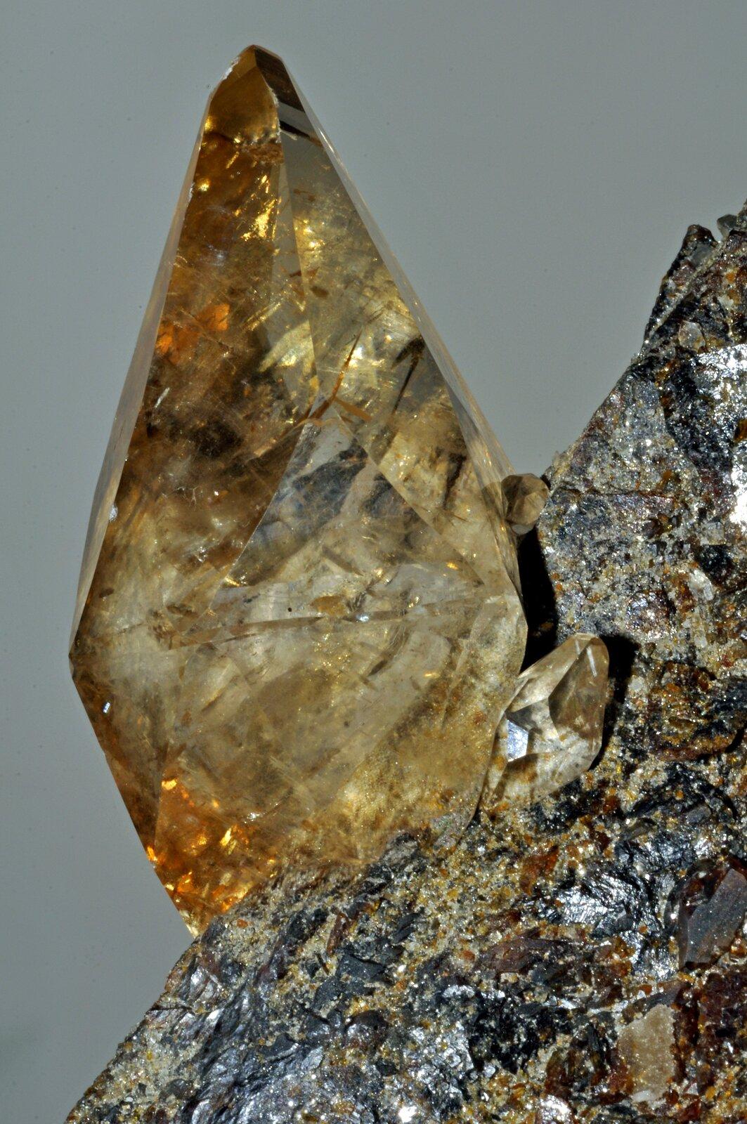 Na zdjęciu minerał. Jest to kalcyt. Tworzy kryształy wkształcie słupków. Jest przezroczysty. Kolor biały, żółty ipomarańczowy.