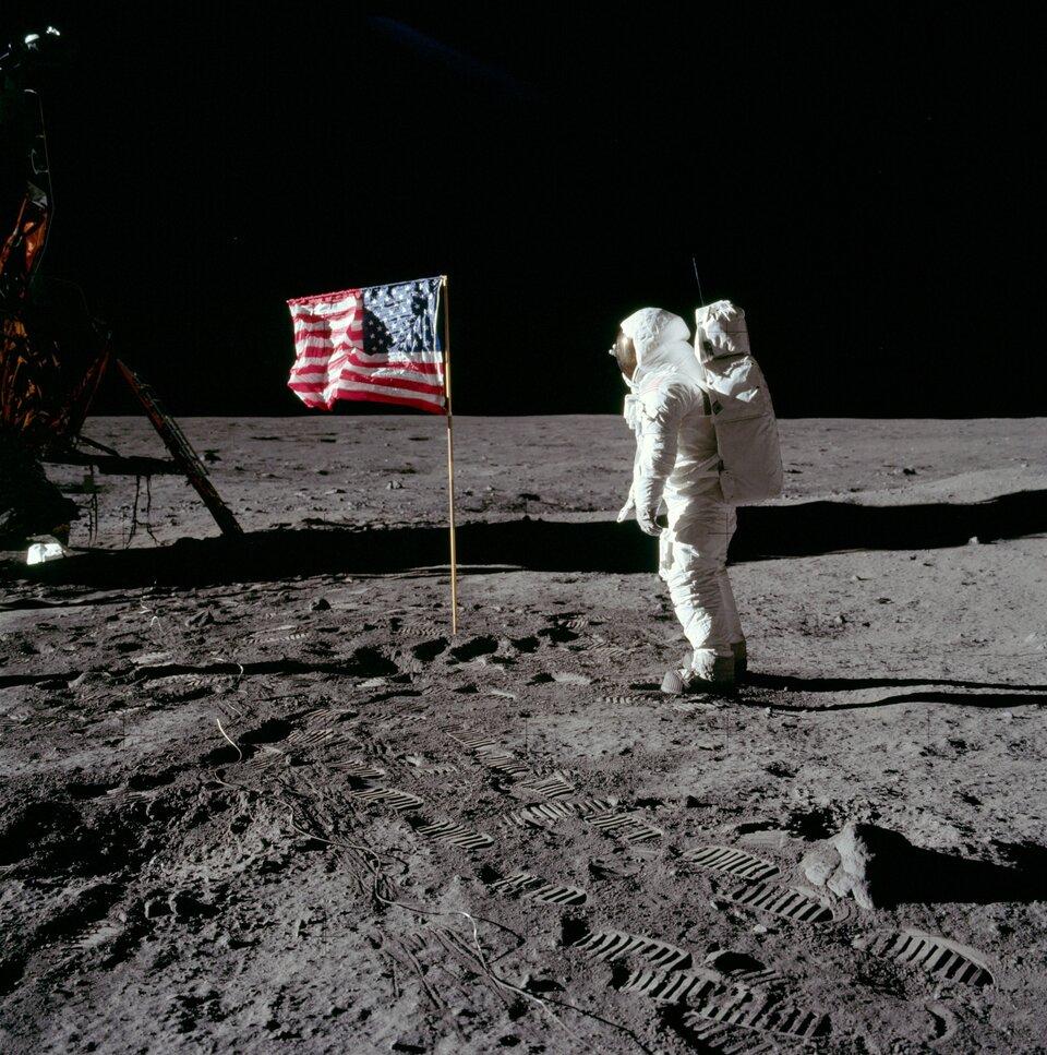 Zdjęcie ze zbiorów Amerykańskiej Agencji Aeronautyki, przedstawiające misję Apollo 11 ipierwsze lądowanie człowieka na Księżycu. Kadr kwadratowy, po lewej stronie widoczny fragment lądownika, centrum kadru zajmują flaga USA oraz salutujący jej astronauta Buzz Aldrin. Wdolnej części kadru wyraźne ślady astronautów na powierzchni Księżyca.