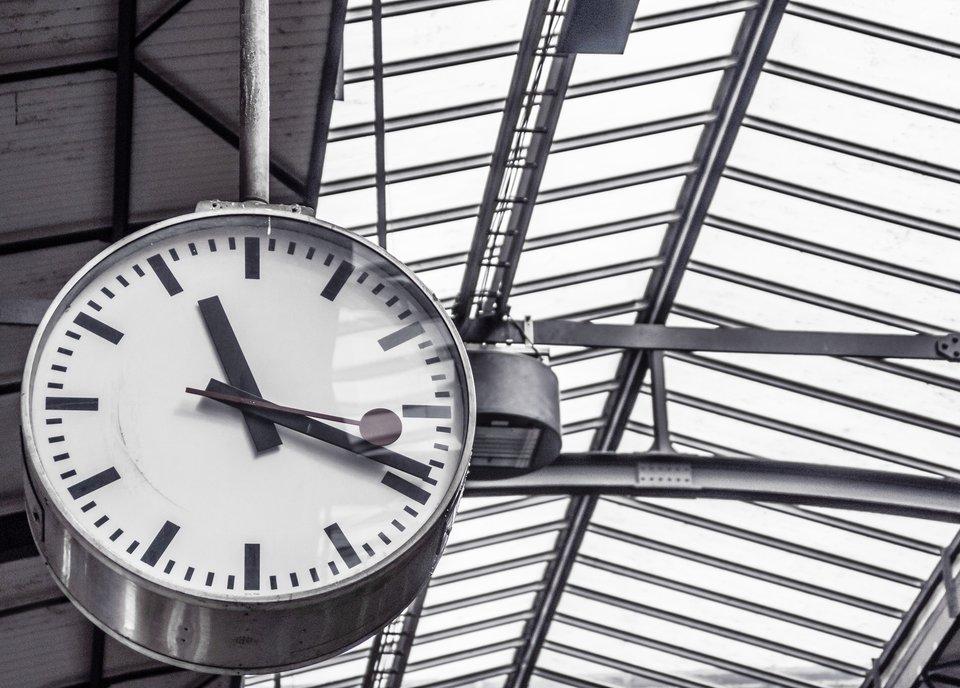 Zegar zsekundnikiem umocowany na metalowych belkach pod szklanym sufitem hali. Zegar jest wykonany zblachy, na białej tarczy wskazówki pokazują godzinę jedenastą dziewiętnaście iosiemnaście sekund. Na tarczy poszczególne godziny oznaczone są kreskami, anie liczbami.