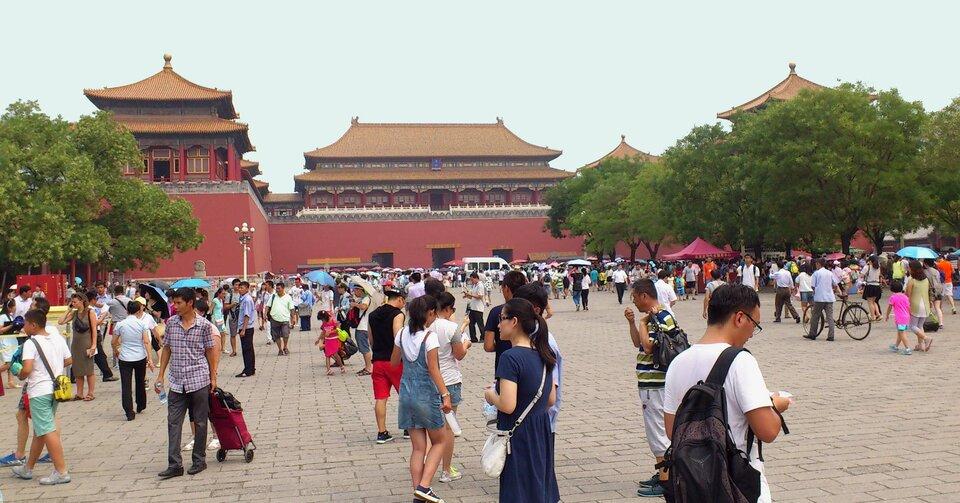 Na zdjęciu kompleks czerwonych budynków ze spadzistymi żółtymi dachami otoczonych czerwonym murem. Duża liczba turystów.