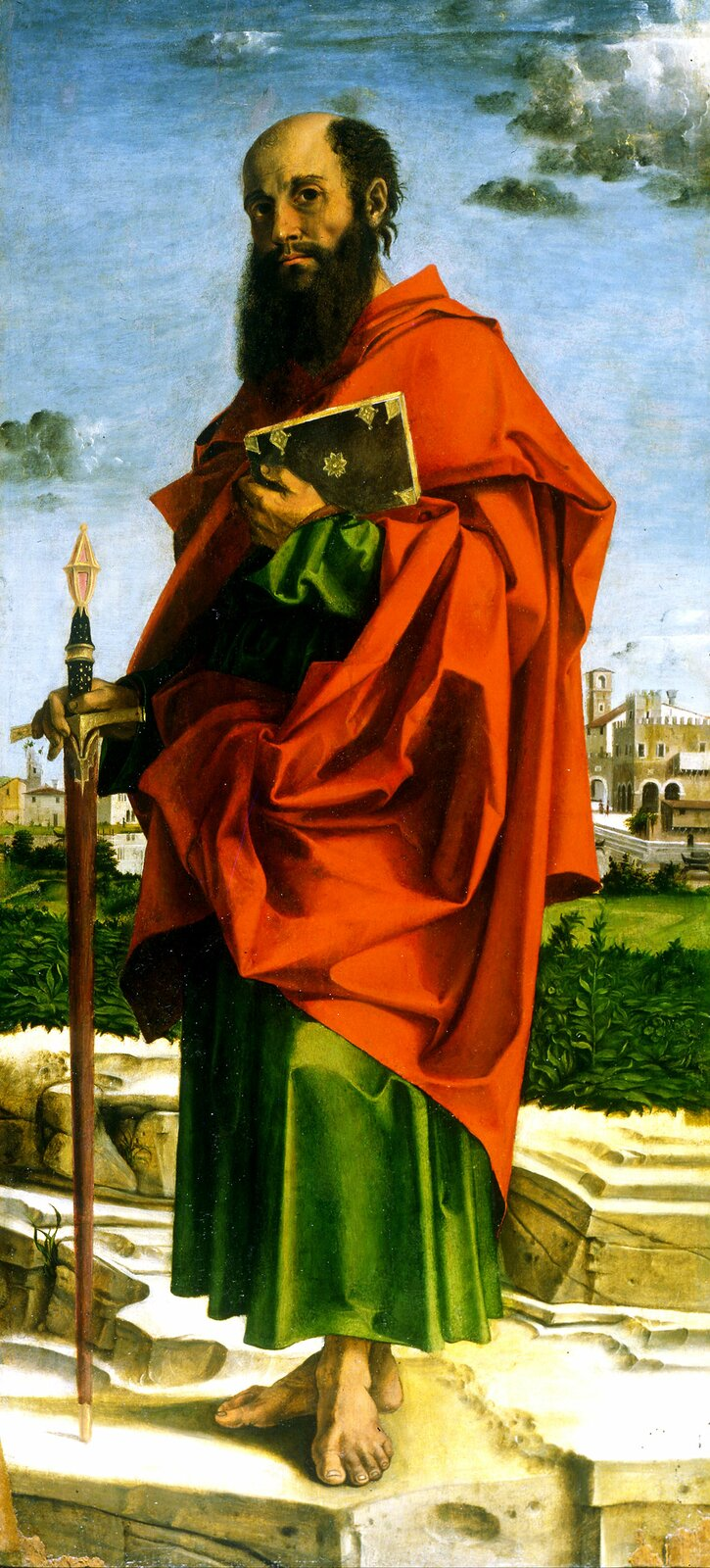Mężczyzna ubrany wczerwono-zieloną szatę, zlaską wjednej ręce, aksięgą wdrugiej ręce stoi na skałach na tle zabudowań miasta woddali.