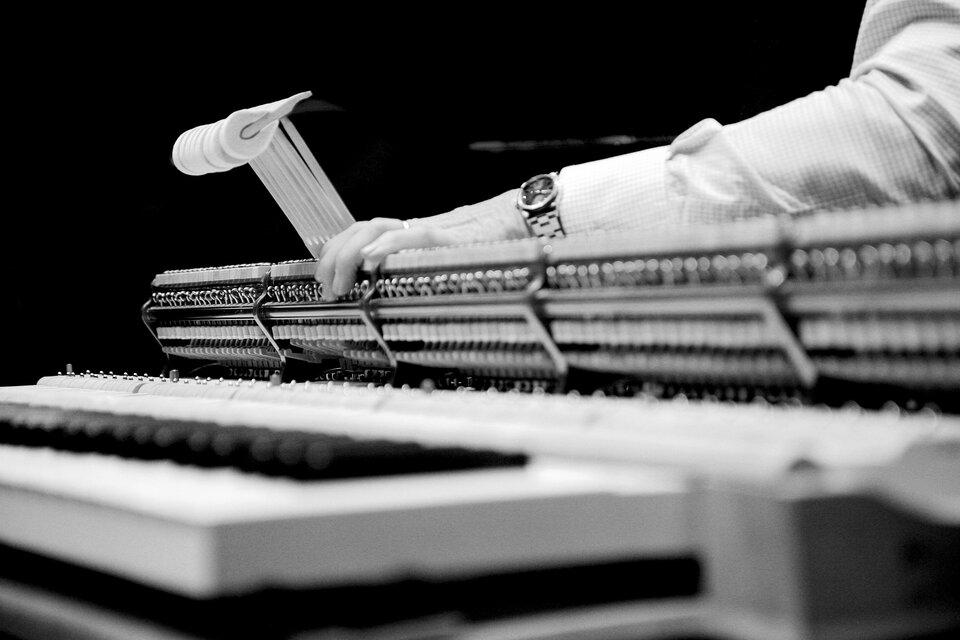 Czarnobiała ilustracja przedstawiająca czynność regulacji mechanizmu fortepianu wyjętego zobudowy. Na pierwszym planie wobszarze nieostrym zdjęcia klawiatura po lewej stronie kadru. Wplanie środkowym mechanizm zmłoteczkami, jedna grupa młoteczków uniesiona wgórę przez osobę dokonującą strojenia. Tło czarne.