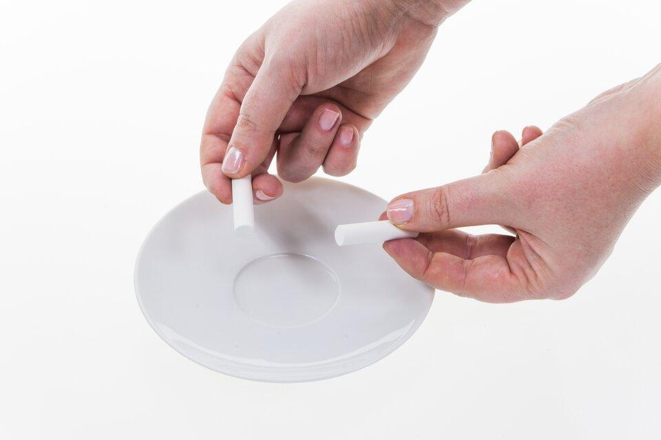Na fotografii przedstawiono dłonie człowieka, który trzyma dwa kawałki kredy nad talerzykiem. Kreda to przykład substancji kruchej, która łatwo się łamie.