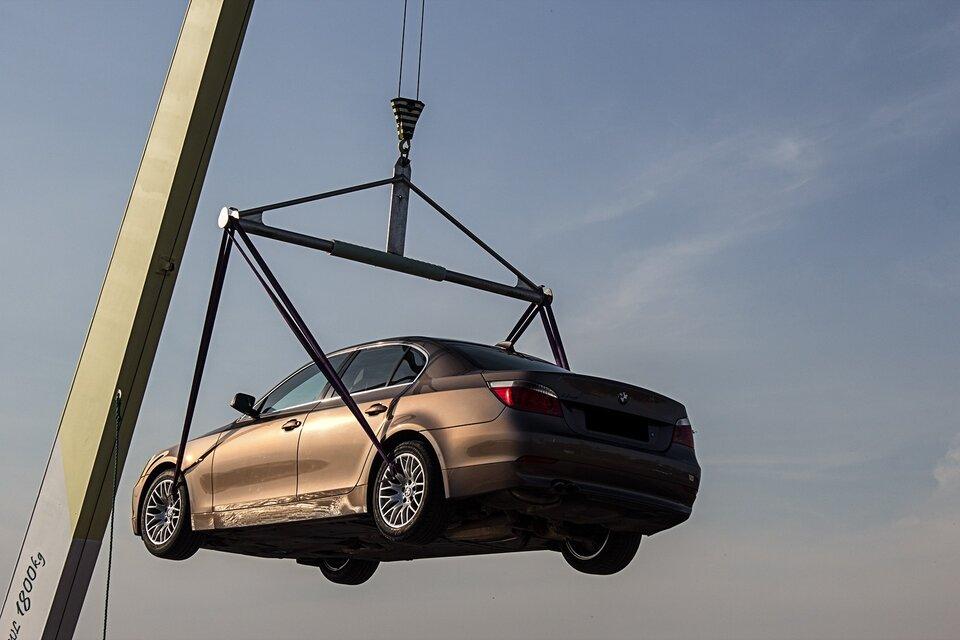 Na ilustracji widać samochód, który został podniesiony przy użyciu dźwigni.