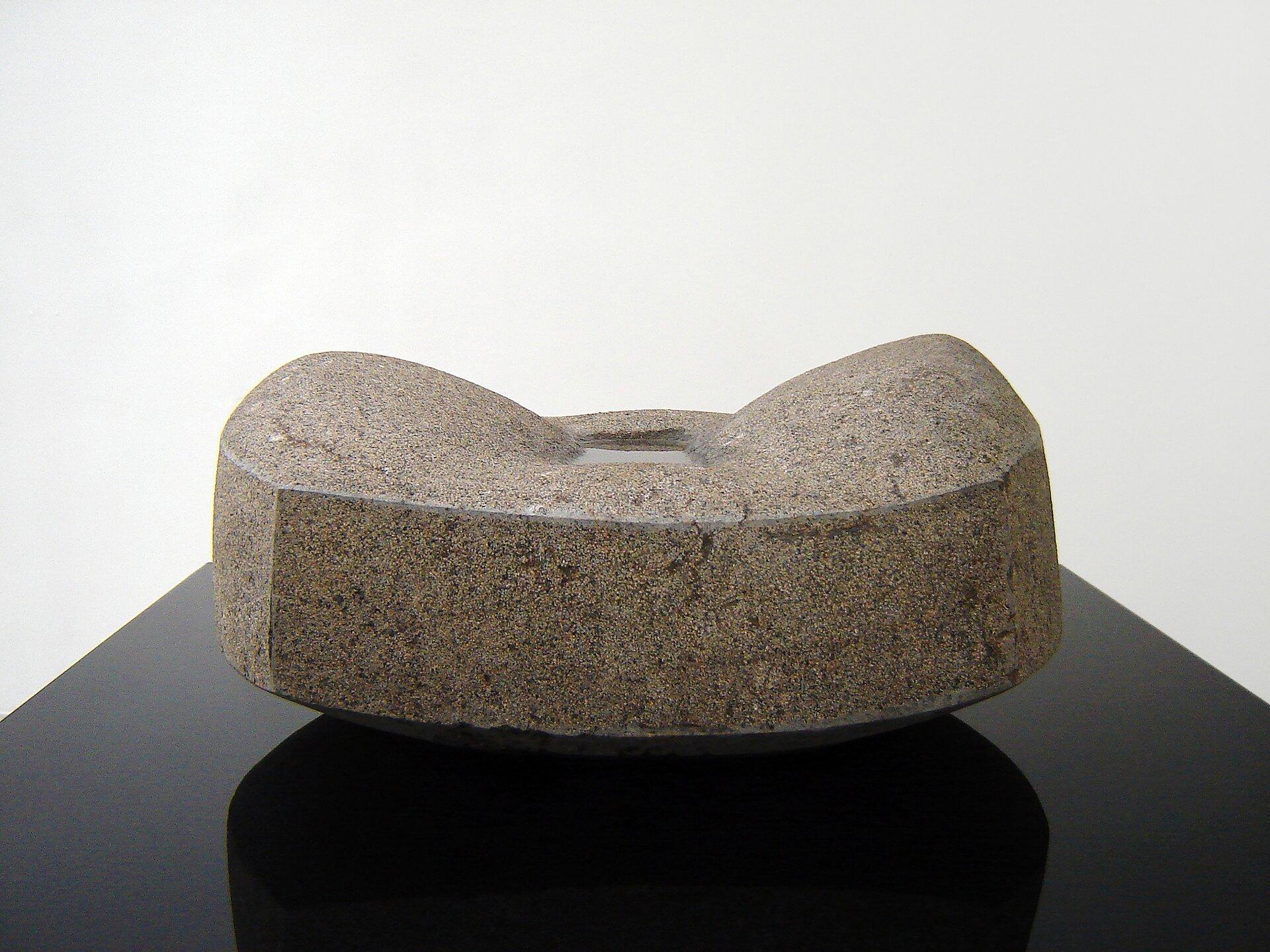 """Ilustracja przedstawia rzeźbę """"Źródło III"""" autorstwa Macieja Wierzbickiego. Na zdjęciu ukazany jest kamienny, nieregularny kształt płaskiego sześcianu zmałym prostokątnym wgłębieniem pośrodku, wktórym znajduje się woda. Obiekt ustawiony jest na gładkim blacie czarnego granitu. Tło stanowi biała płaszczyzna."""