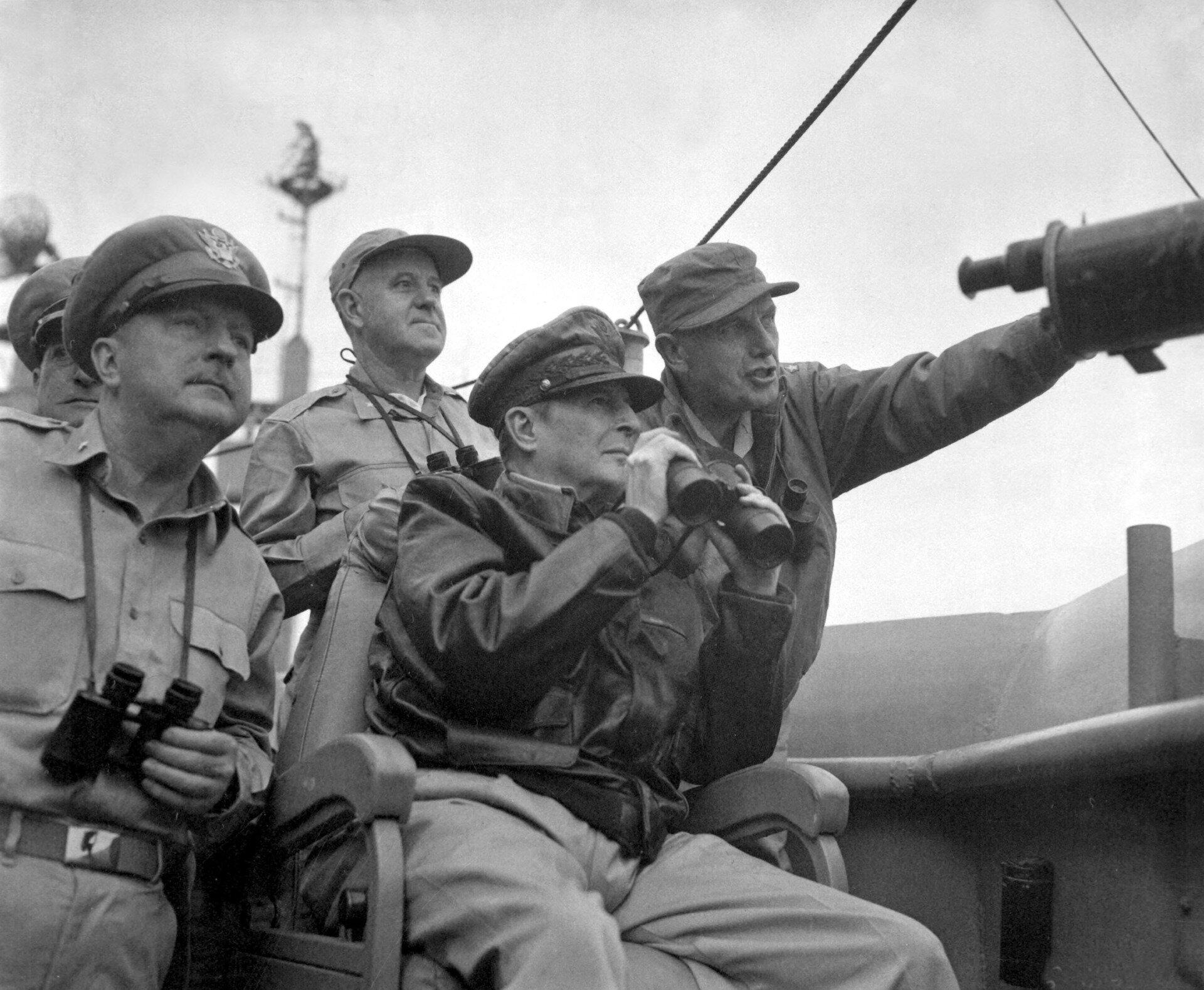 Fotografia czarno-biała przedstawiająca siły ONZ (amerykańskie) , którymi dowodził generał Douglas MacArthur. Dowódca siedzi na krześle,  wrękach trzyma lornetkę. Każdy zobecnych przy nim obserwujący również ma swoją lornetkę, jeden znich wskazuje ręką kierunek wktórym należy patrzeć.