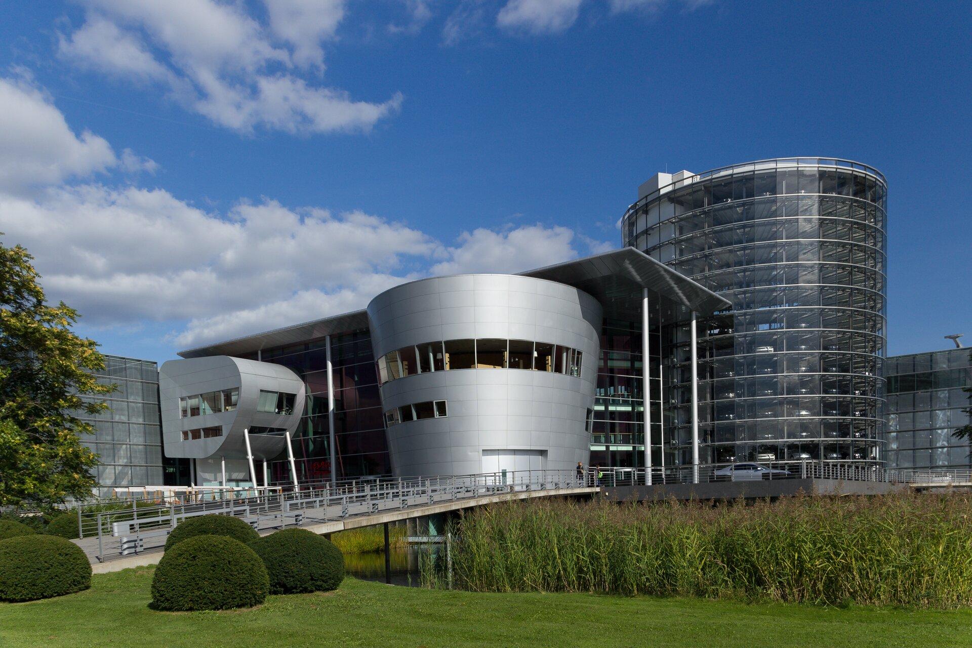 Zdjęcie przedstawia Szklaną Manufakturę wDreźnie, jedną zfabryk koncernu Volkswage. Budynek ma nowoczesny kształt pełen efektownych linii krzywych, acała jego główna część wraz zwieżą po prawej stronie pokryta jest wyłącznie szkłem.