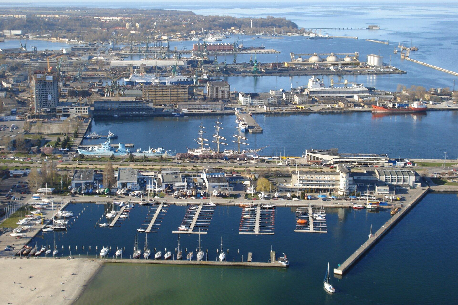 Na zdjęciu lotniczym zabudowania portowe. Kilka basenów portowych wkształcie wąskich prostokątów zbetonowymi nabrzeżami uzbrojonych wdźwigi, magazyny. Zacumowane statki, jachty, łodzie.