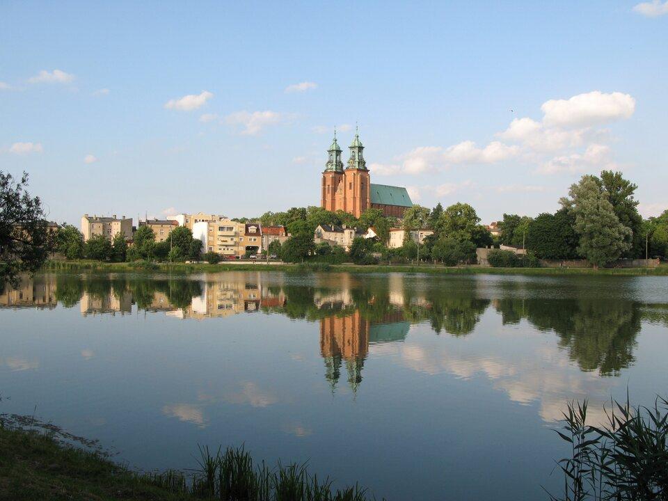 Na zdjęciu wysoki kościół zdwoma wieżami izabudowa miejska nad brzegiem rzeki.