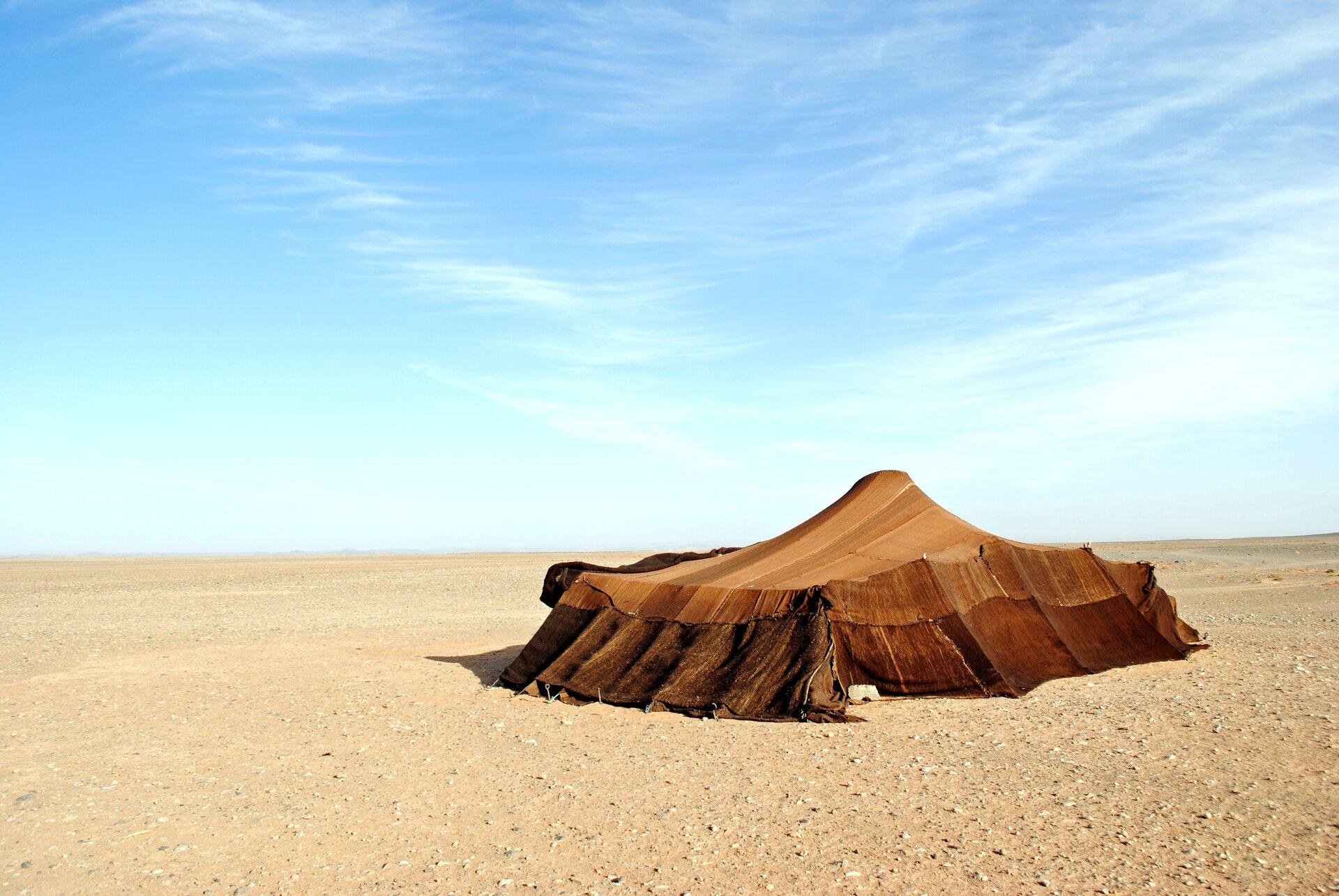 Namiot na pustyni. Podłoże jest kamieniste ipozbawione roślin. Na środku zdjęcia widać duży namiot, wktórym może schronić się kilkanaście osób.