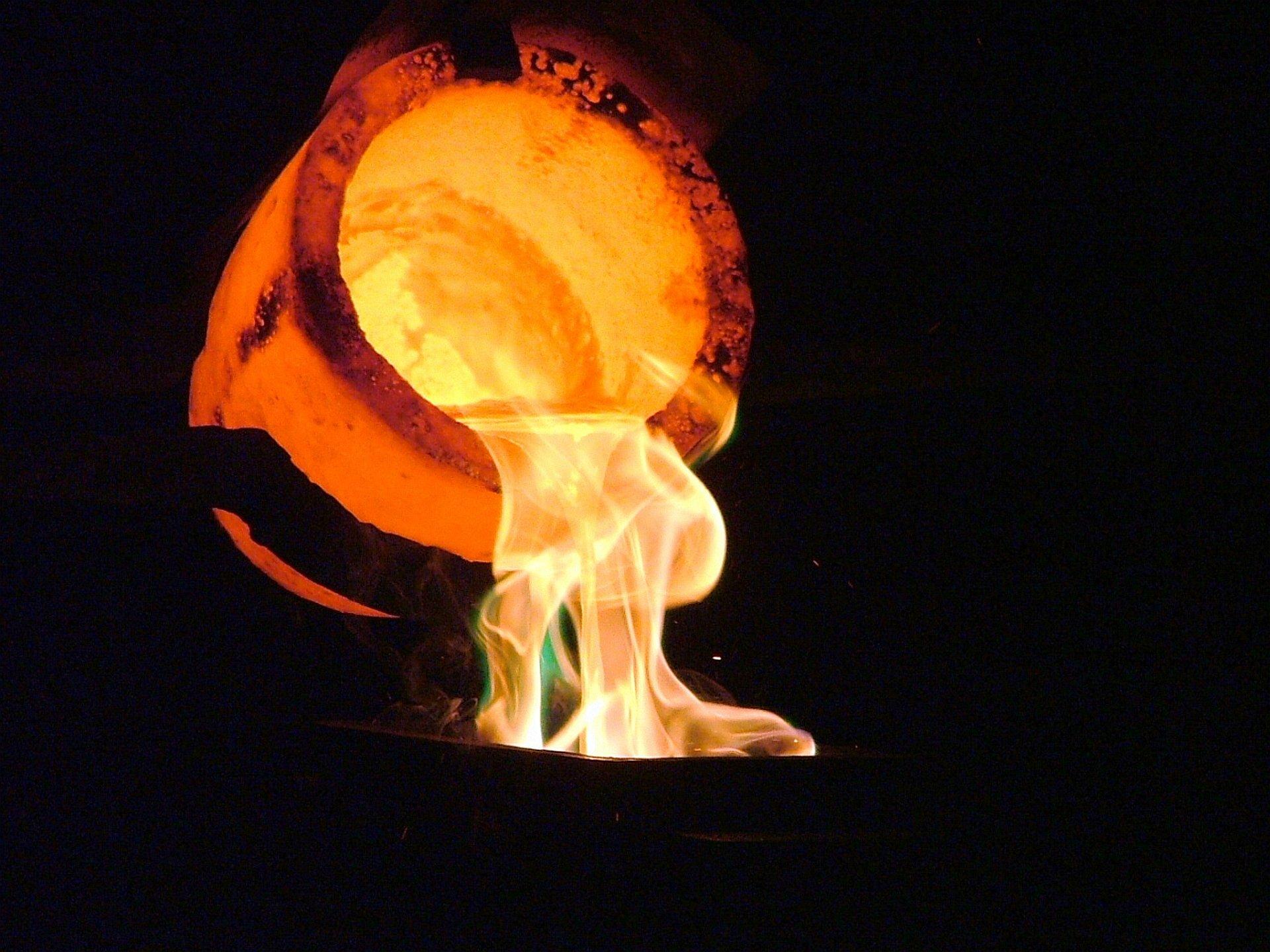 Zdjęcie przedstawia rozżarzony do czerwoności tygiel, zktórego po obróceniu wypływa struga płynnego złota otaczana przez płomienie. Całe otoczenie tygielka jest ciemne, co sugeruje, że tak naprawdę blask zarówno tygielka jak izłotej strugi są znacznie jaśniejsze.
