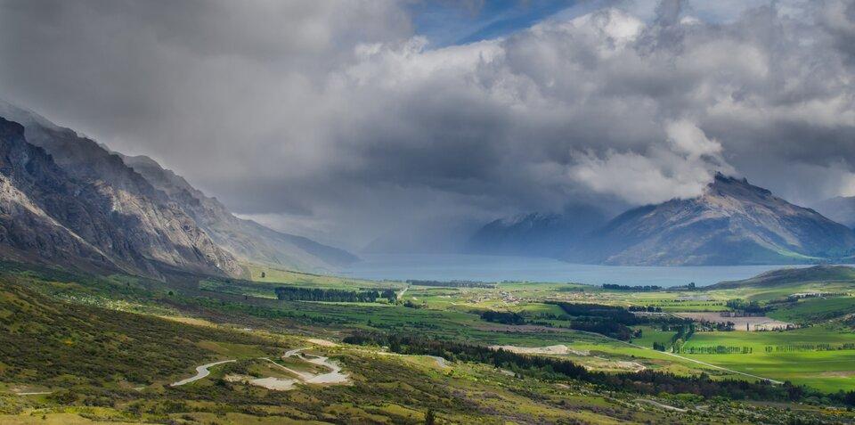 Na zdjęciu krajobraz Nowej Zelandii. Na pierwszym planie rozległa równina pokryta trawą, gdzieniegdzie drzewa. Kręta droga. Po lewej stronie wysokie strome góry. Nie są pokryte roślinnością. Wtle zbiornik wodny igóry. Niebo pokryte szarymi chmurami przykrywającymi szczyty gór.