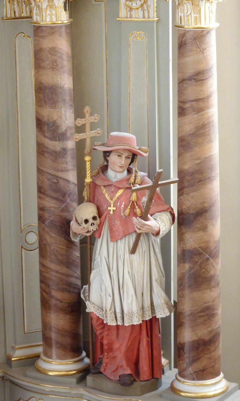Rzeźba św. Karola Boromeusza wstroju kardynalskim Figurazdawnego klasztoru cystersów wWehlen wNadrenii-Palatynacie. Święty pokazany został wstroju kardynalskim. Godność tę otrzymał od swojego wuja papieża Piusa IV. Źródło: GFreihalter, Rzeźba św. Karola Boromeusza wstroju kardynalskim, 2012, fotografia, licencja: CC BY-SA 3.0.
