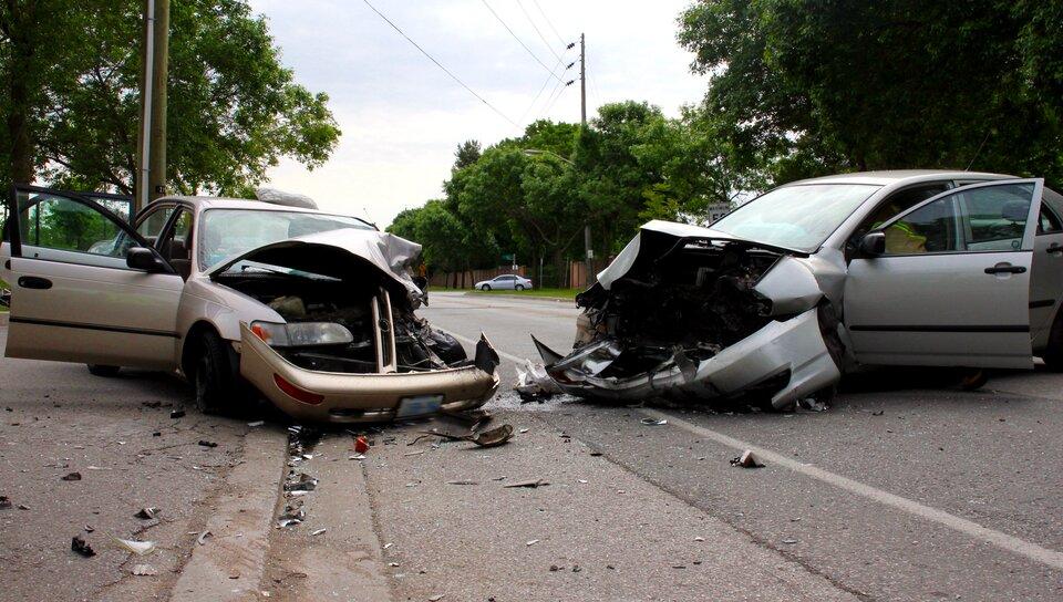 Zdjęcie przedstawia dwa zniszczone samochody na skutek kolizji. Wtle ulica oraz drzewa. Niebo jasne. Maski obu aut są wcałości zgniecione. Zderzaki odpadły. Na ulicy widać leżące fragmenty potłuczonych reflektorów oraz elementów karoserii.