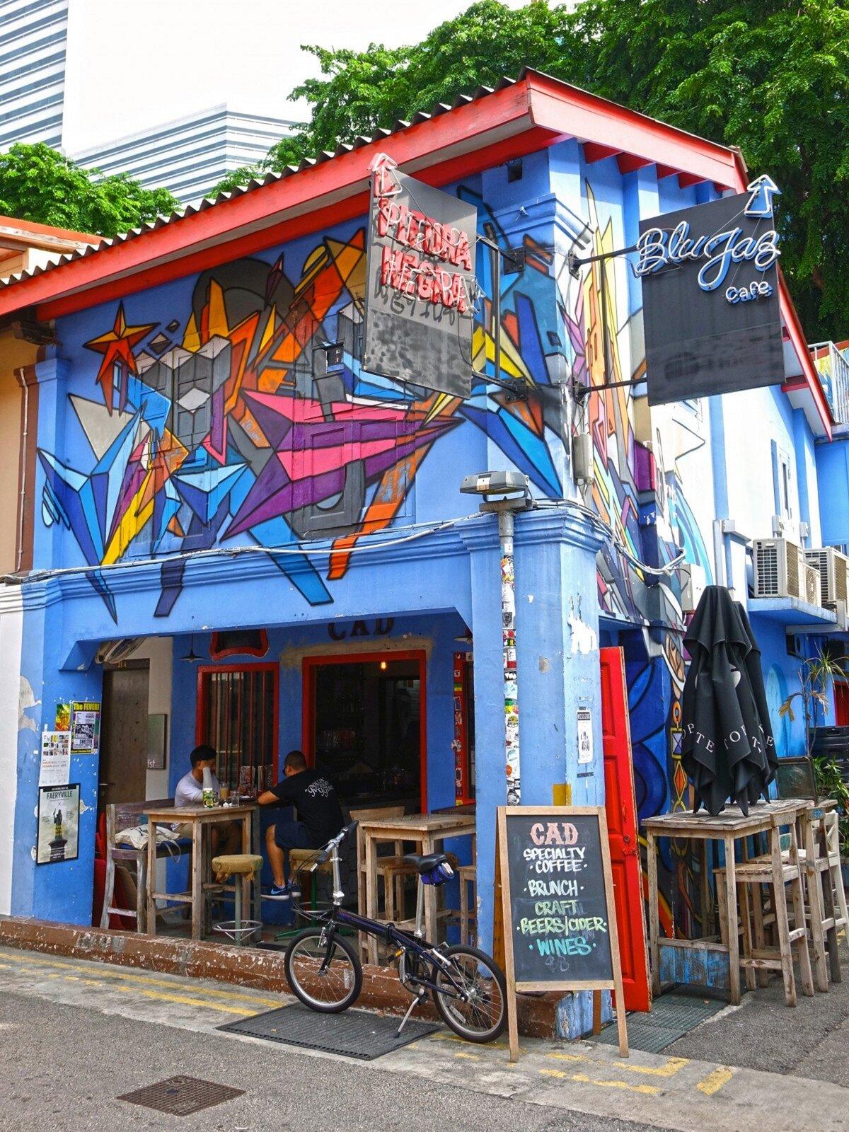 Zdjęcie przedstawia graffiti namalowane na fasadzie niebieskiego budynku zczerwonym dachem. Graffiti ukazuje kolorowe wzory geometryczne. Przed budynkiem stoi rower. Budynek ze zdjęcia to najprawdopodobniej restauracja. Przed budynkiem stoją stoliki oraz krzesła, na których siedzą dwie postacie.