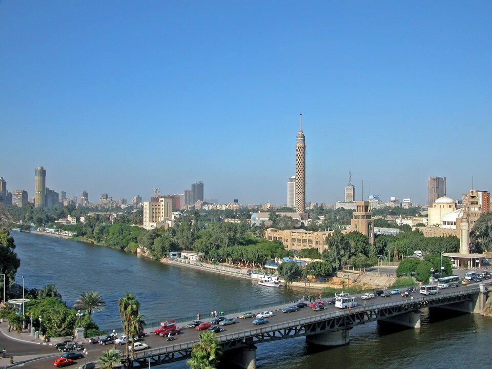 Na zdjęciu szeroka rzeka, na pierwszym planie most, dużo samochodów. Brzegi porośnięte drzewami. Wtle duże miasto, liczne budynki. Kilka wysokich budynków iwież. To Kair.